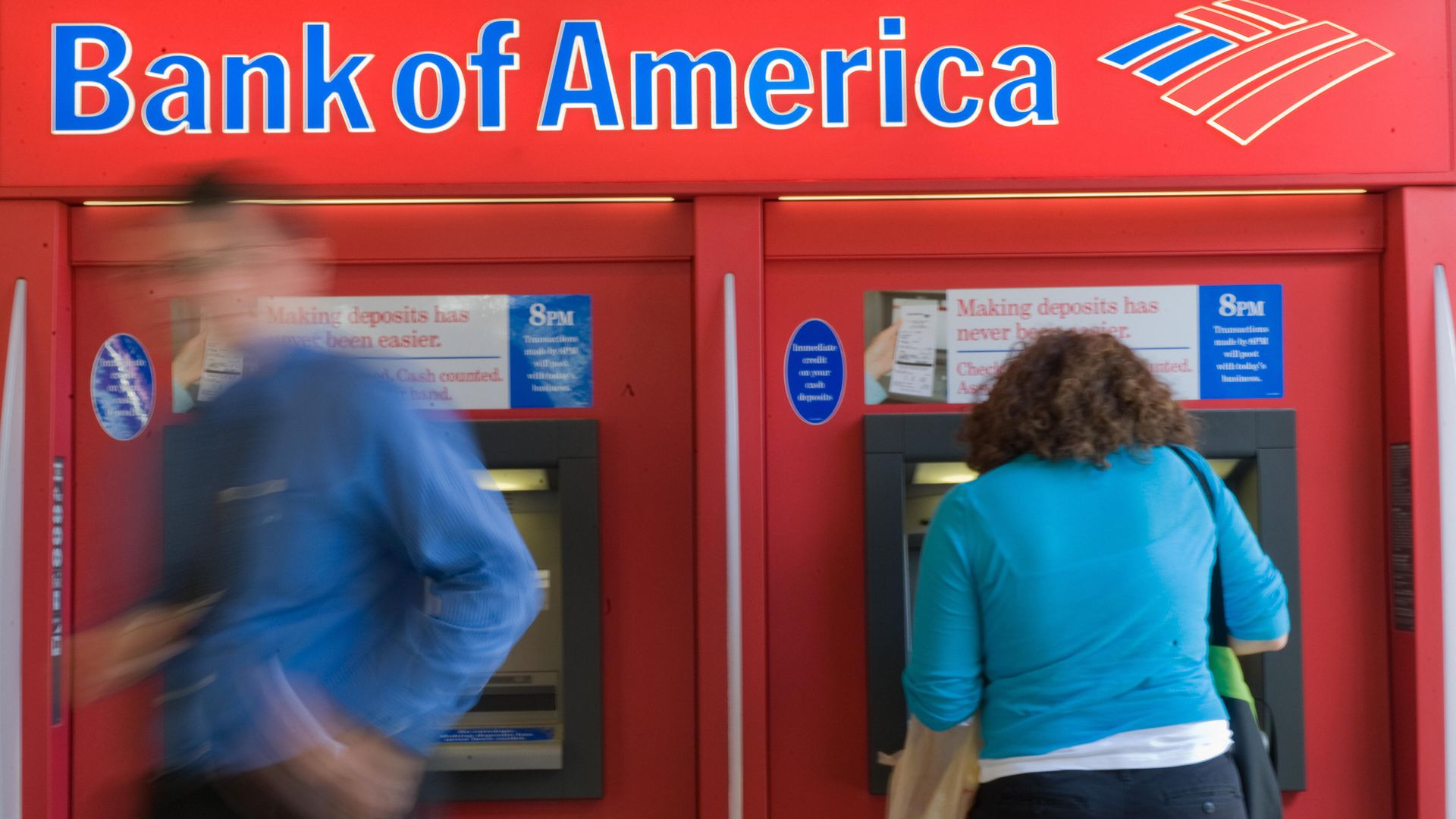 People use a Bank of America automatic teller machine.