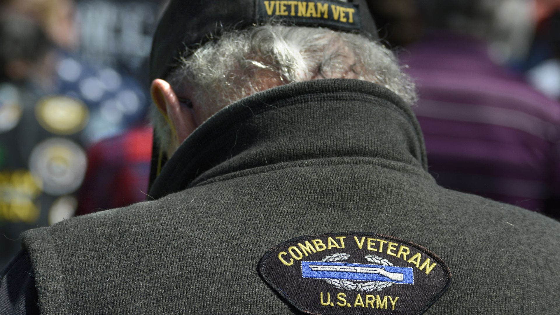 Photo of a man wearing a vest and a hat with Vietnam veteran patches