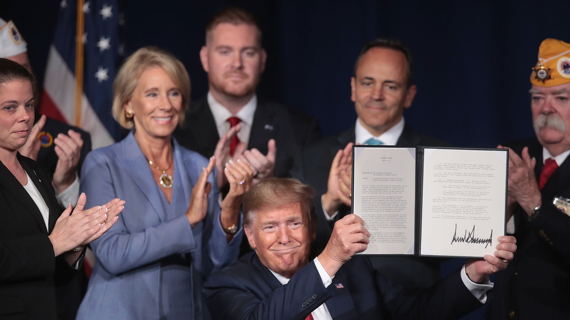 President Donald Trump signs a proclamation that will eliminate student loan debt for qualifying disabled veterans following a speech at the American Veterans