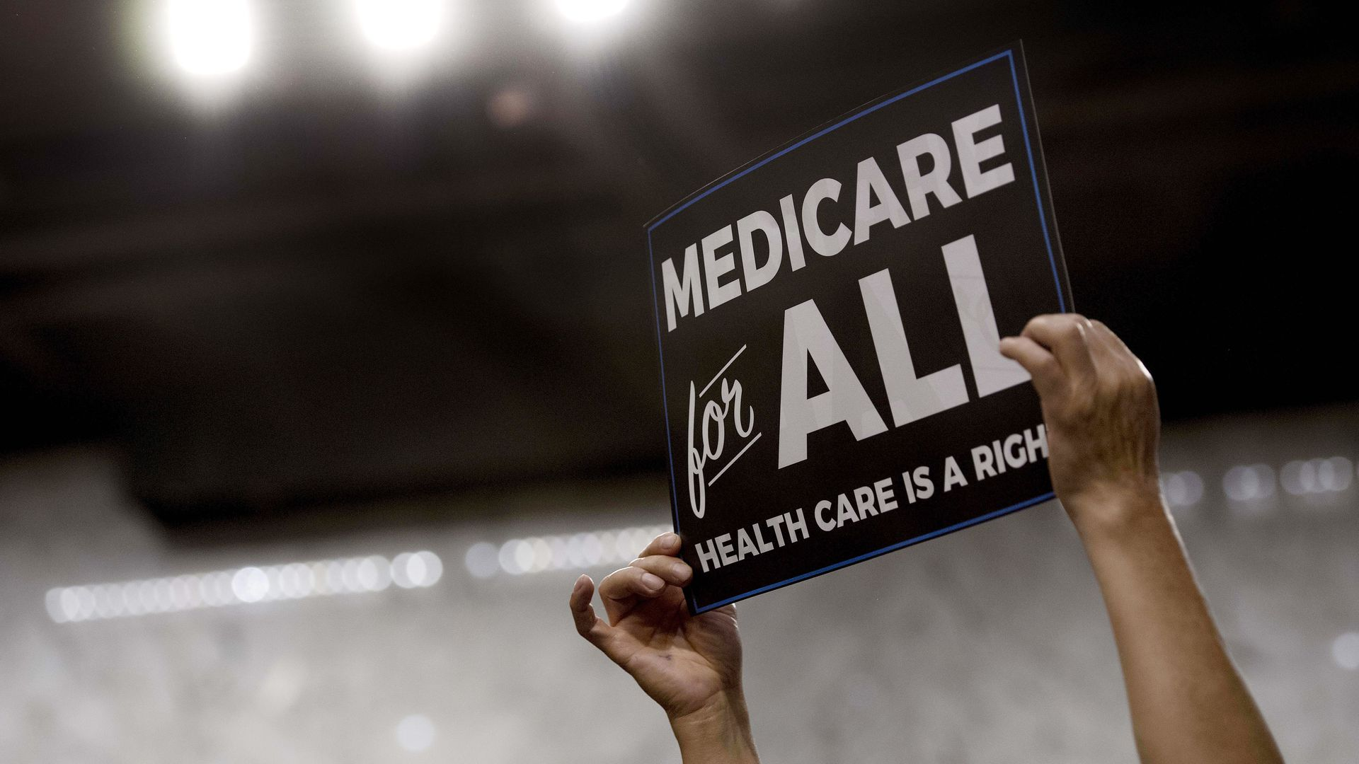 "Someone holds up a sign that reads, ""Medicare for all"""