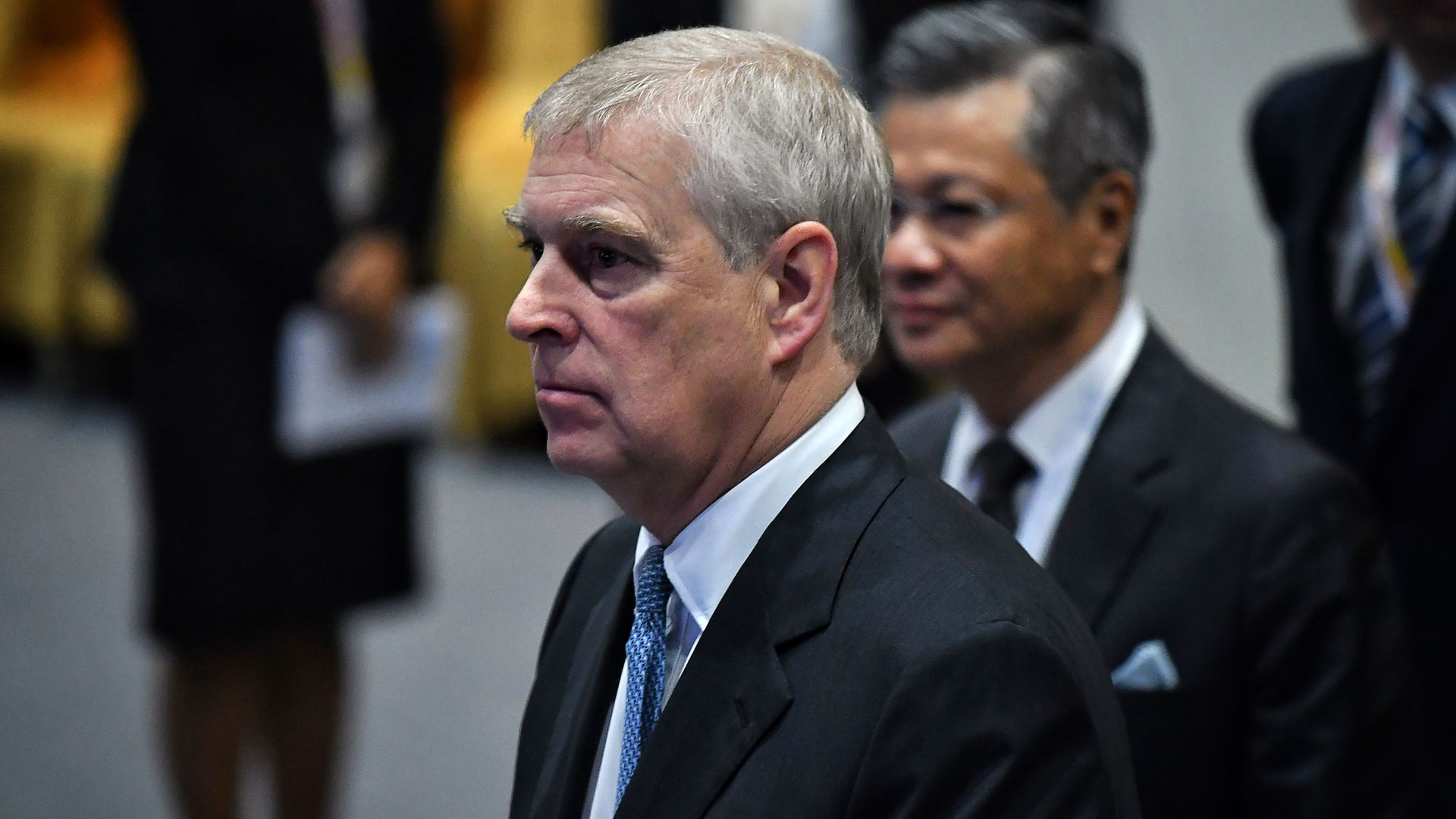 In this image, Prince Andrew stands and walks while wearing a suit.