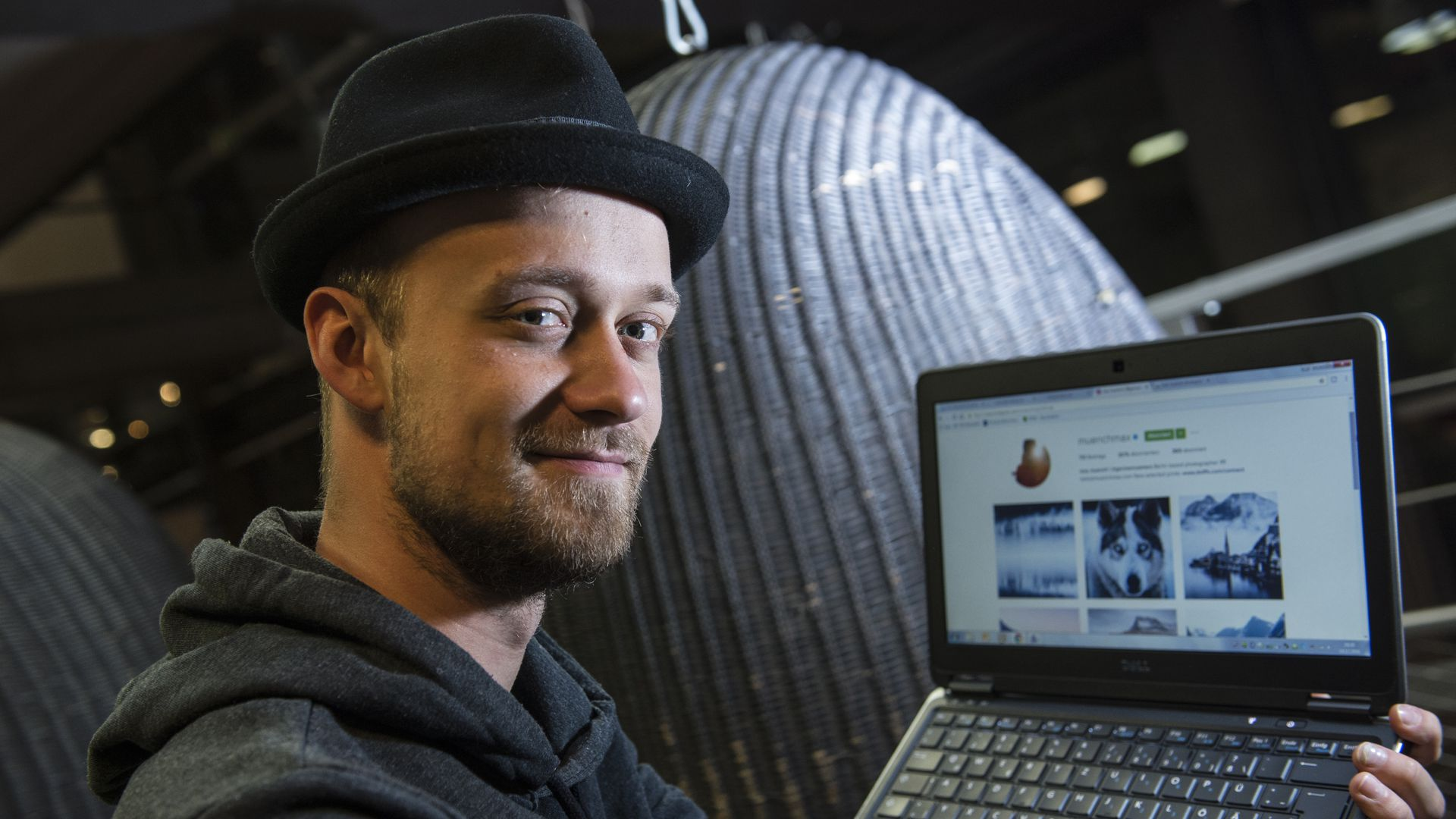 A man in a fedora shows off a laptop that's open to Instagram