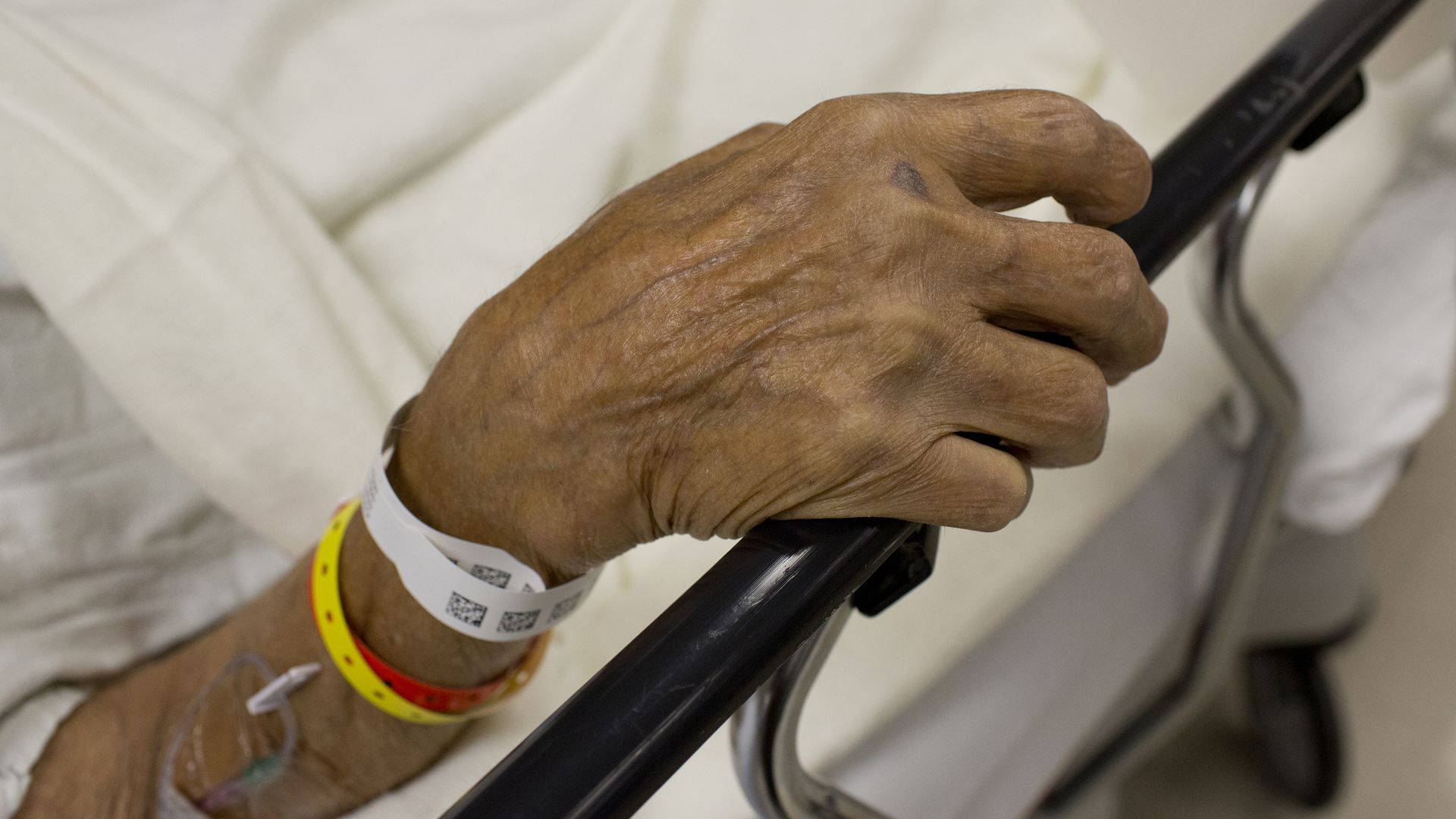 Old man's hand with hospital bracelets