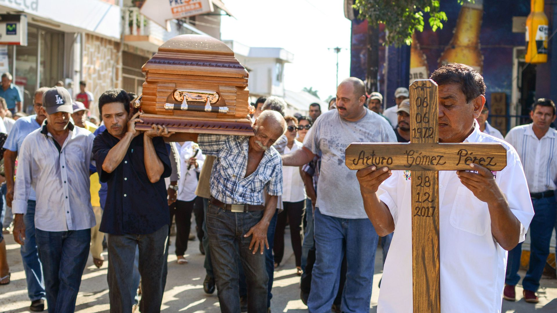 People carry a wooden coffin and wooden cross in Mexico down the street.