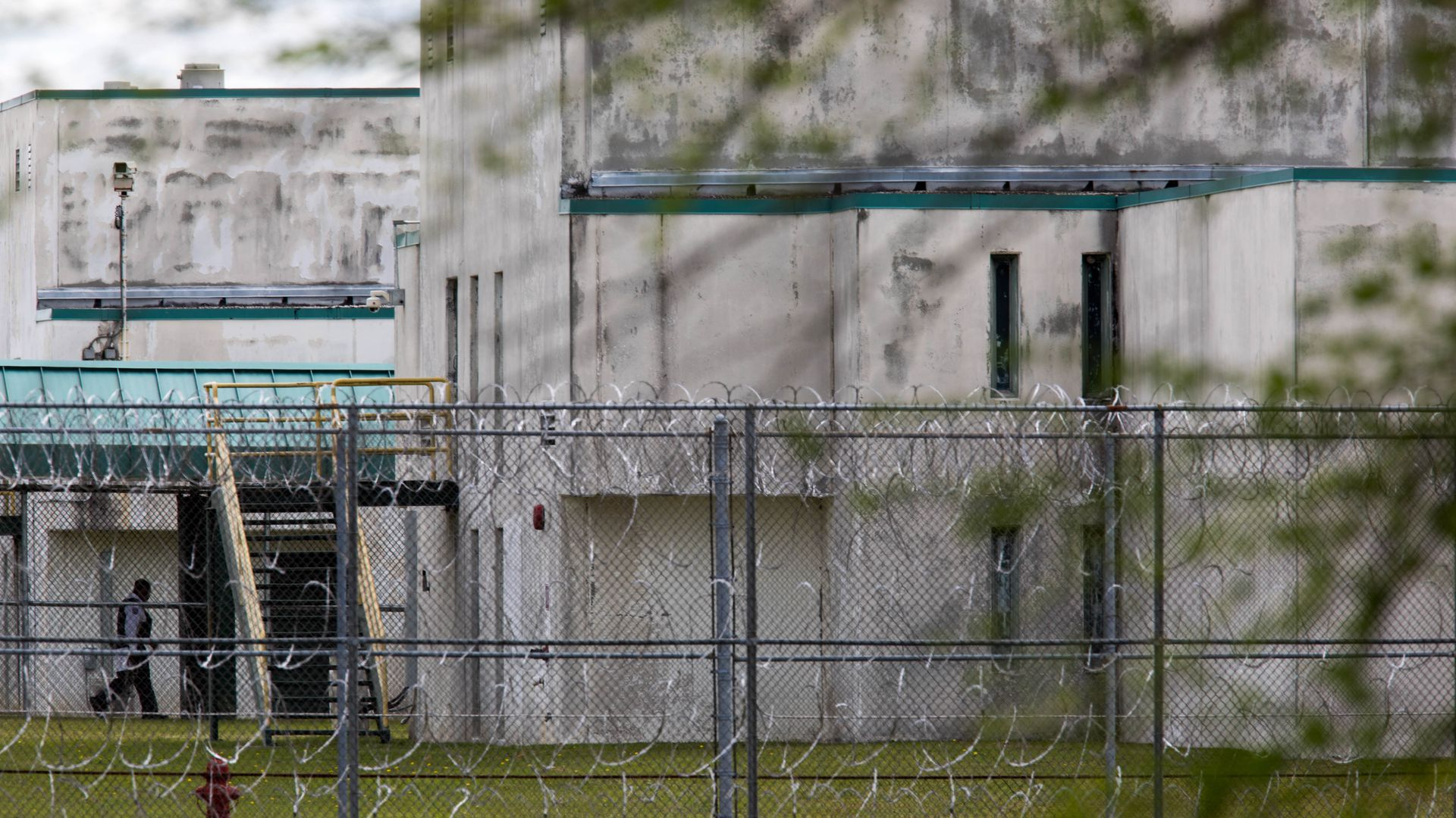 A prison guard runs into a correctional center viewed through a chainlink fence