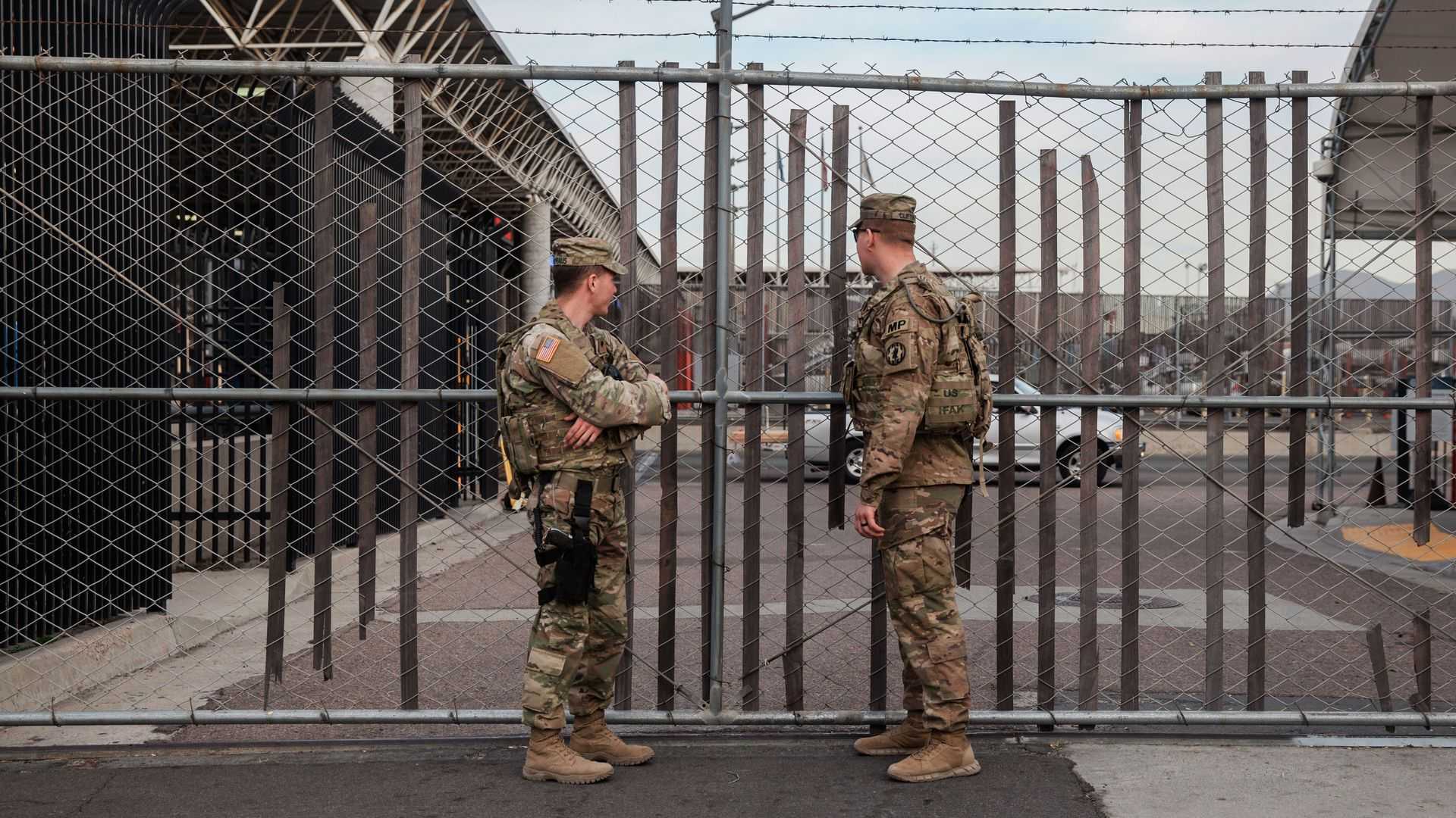 U.S. troops stand at a gate.