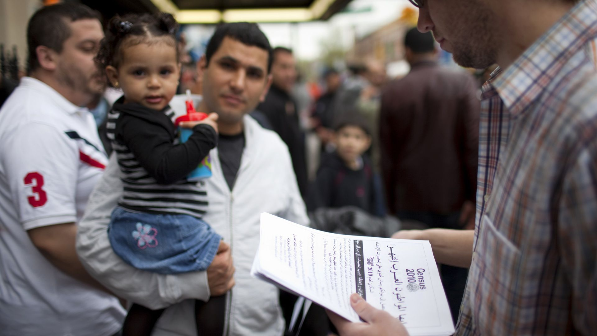 In this image, a man holds a toddler while another man hands out census papers.