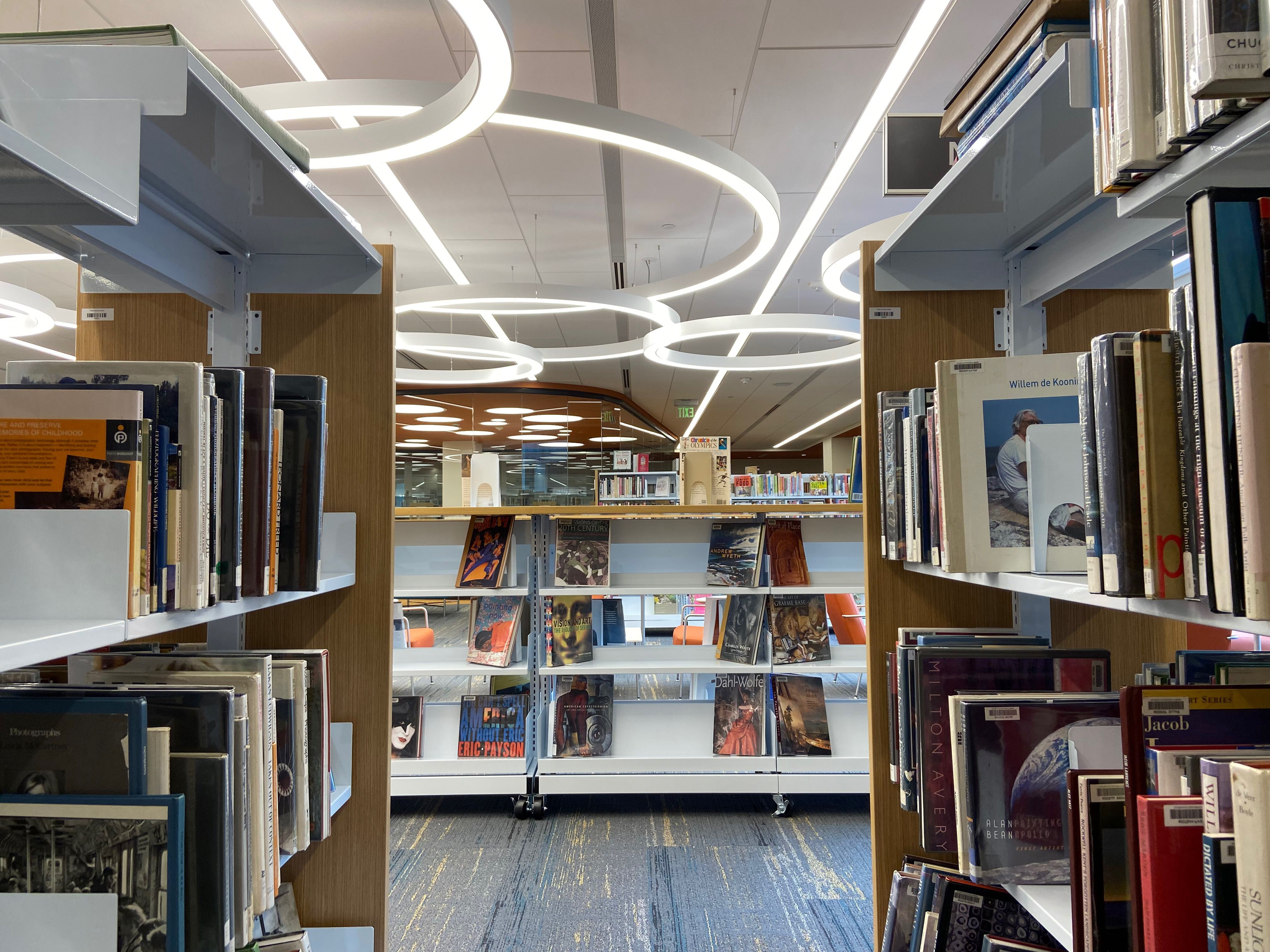 A perspective from between the aisles of books, looking out to a room with circular lighting fixtures overhead