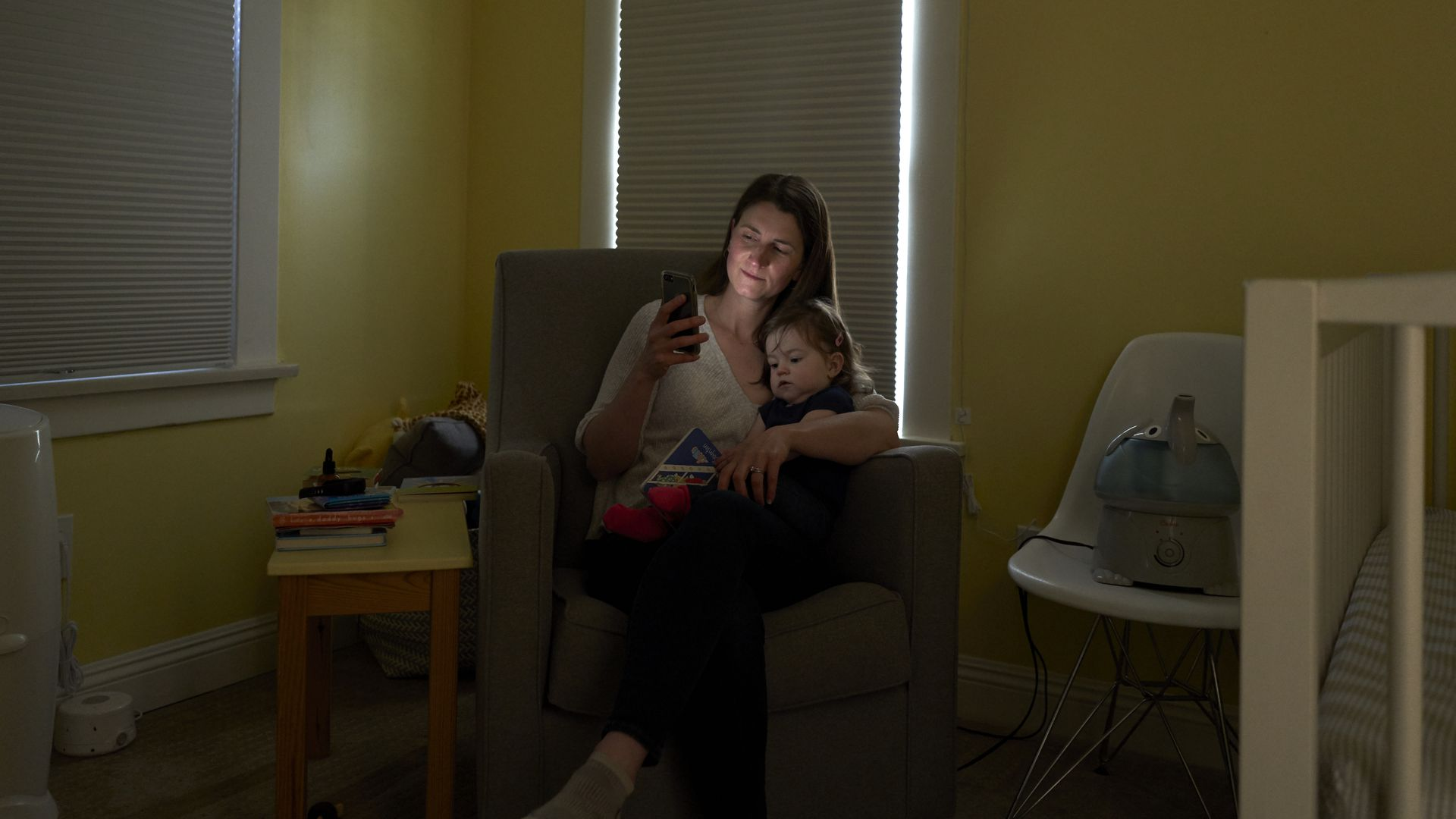 In this image, a mother looks at her phone while holding her infant in her lap in a chair in the corner of a nursery.