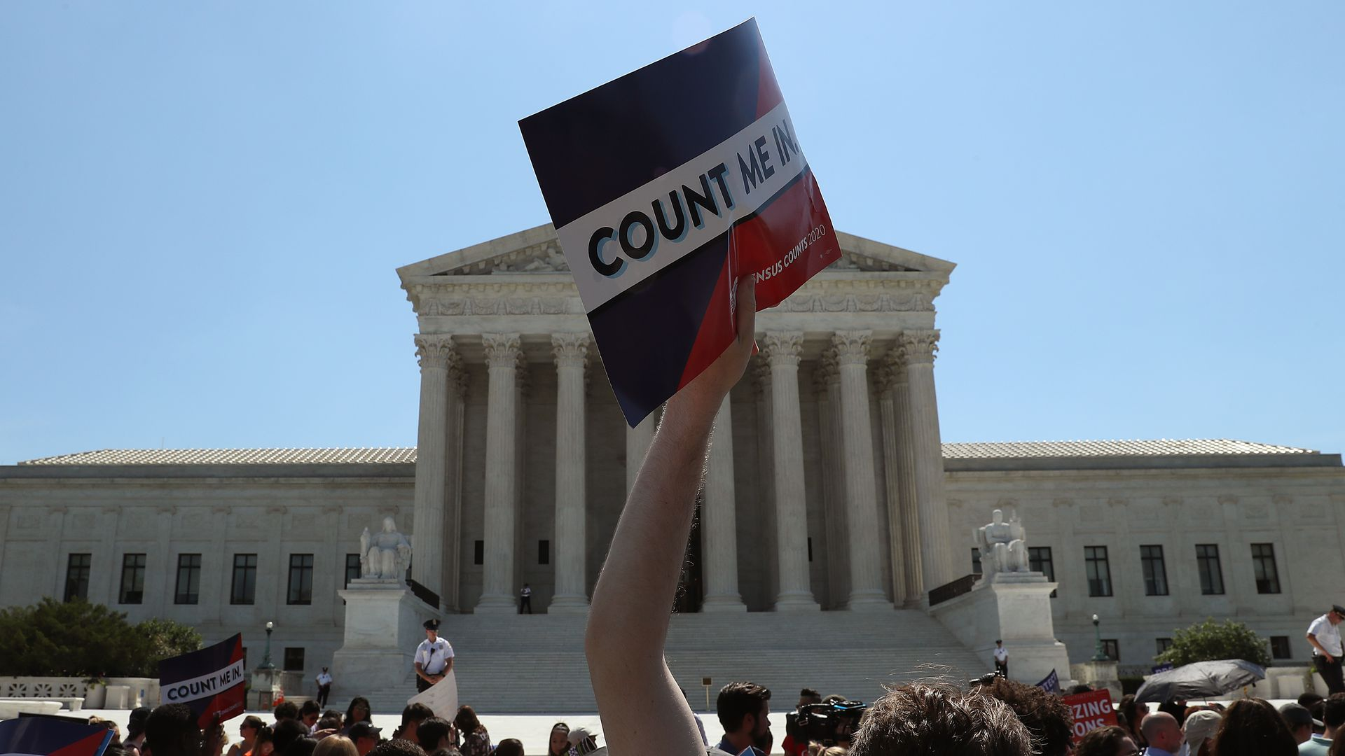 "This image shows a man holding a ""Count Me in"" sign in front of the Supreme Court at a protest."