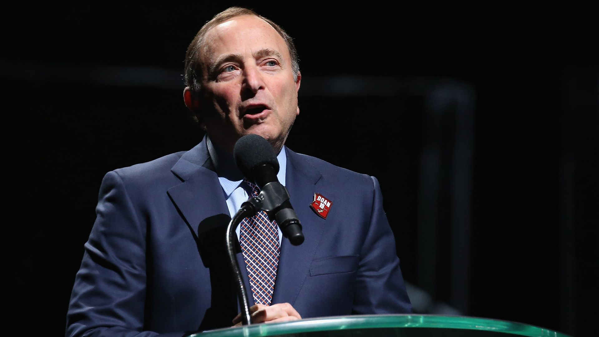 NHL commissioner Gary Bettman stands and speaks in a suit in front of a podium.