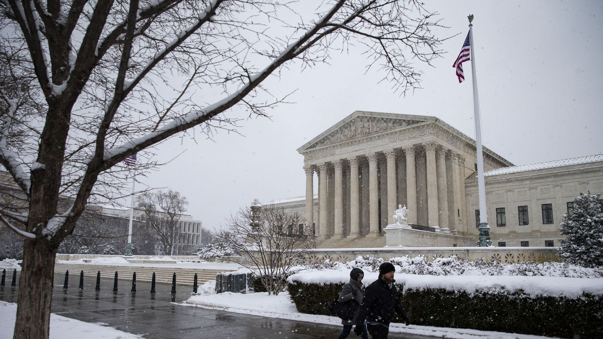 In this image, pedestrians walk on a snowy sidewalk in front of the Supreme Court.
