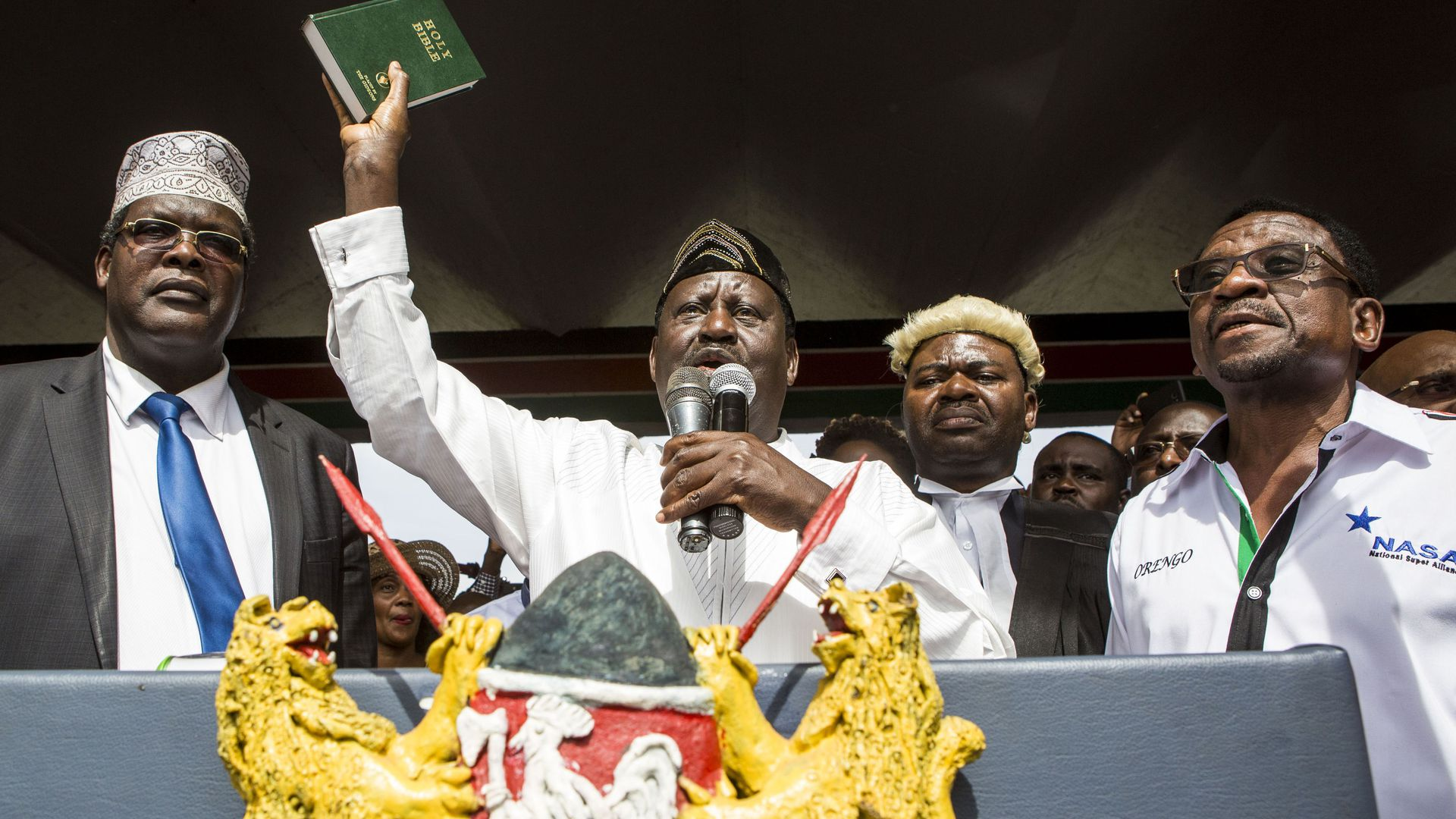 Odinga with Bible raised while speaking at lectern
