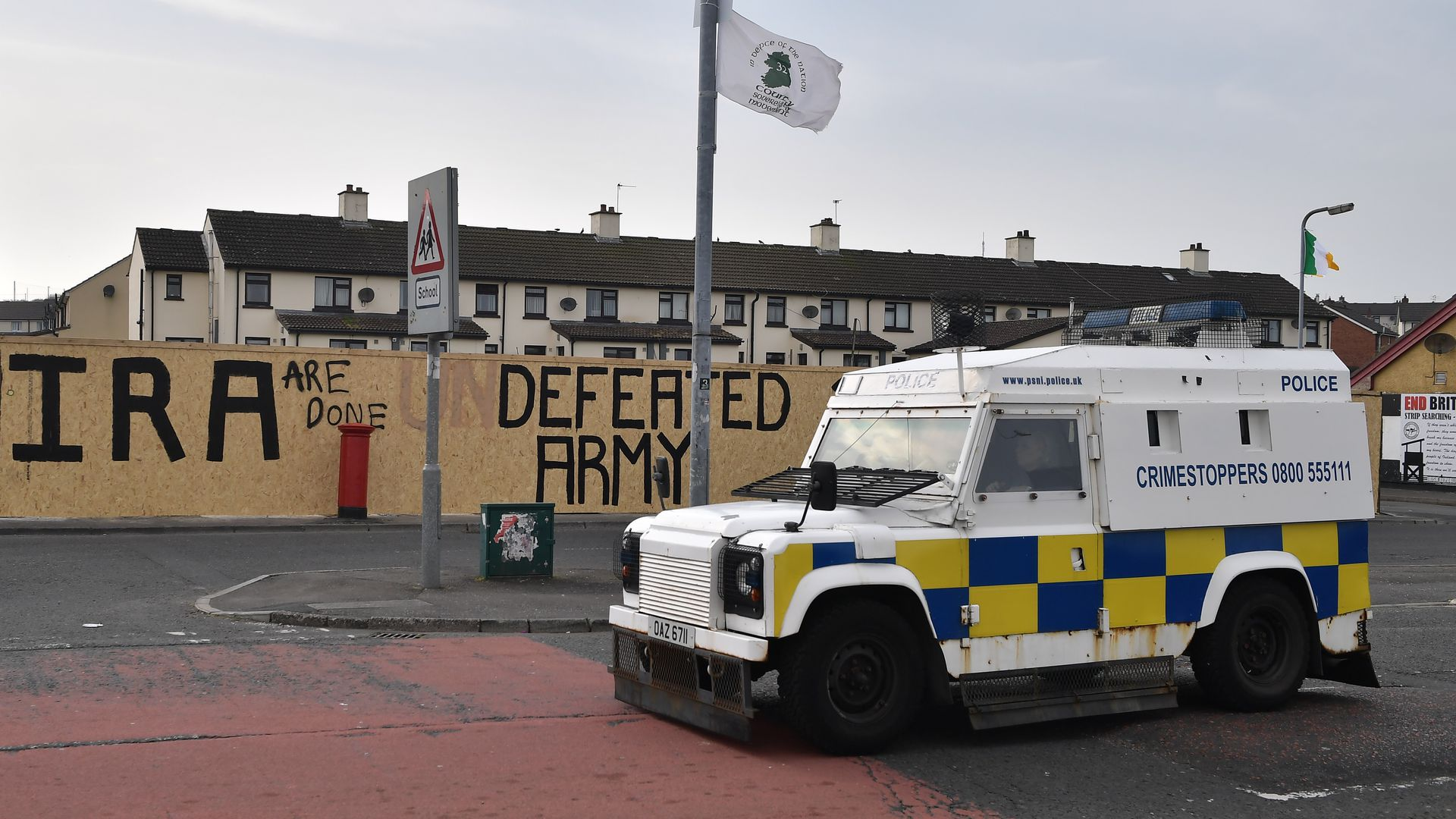 "In this image, an ambulance is parked on a street with a wall behind it that reads ""IRA are done: Defeated Army"""