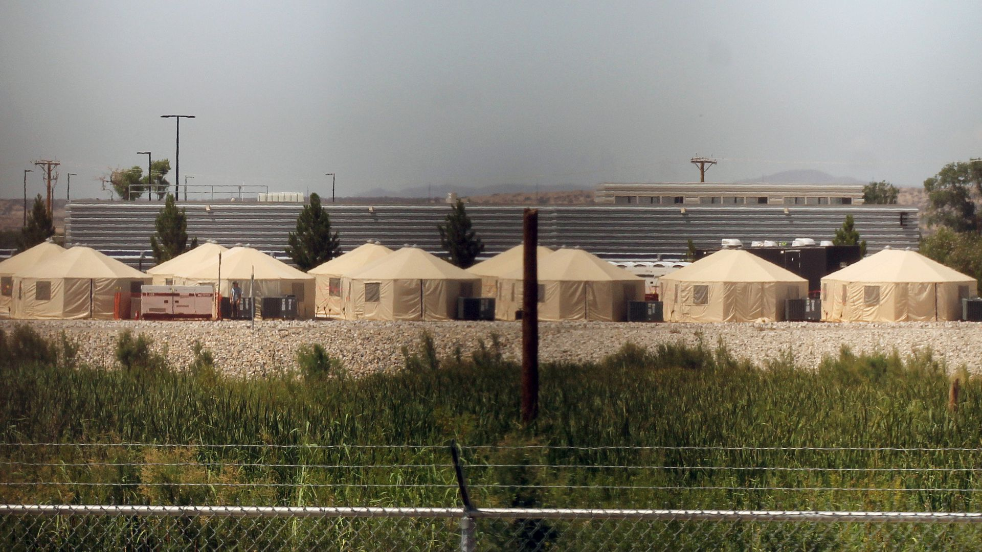 Tents set up behind a barbed wire fence that are used for detaining immigrants.