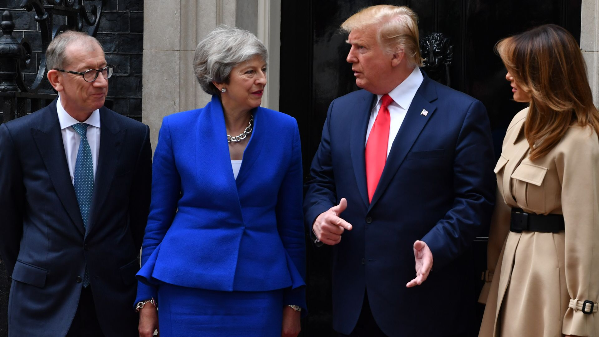 In this image, May and Trump talk while standing next to their spouses in front of Downing Street.