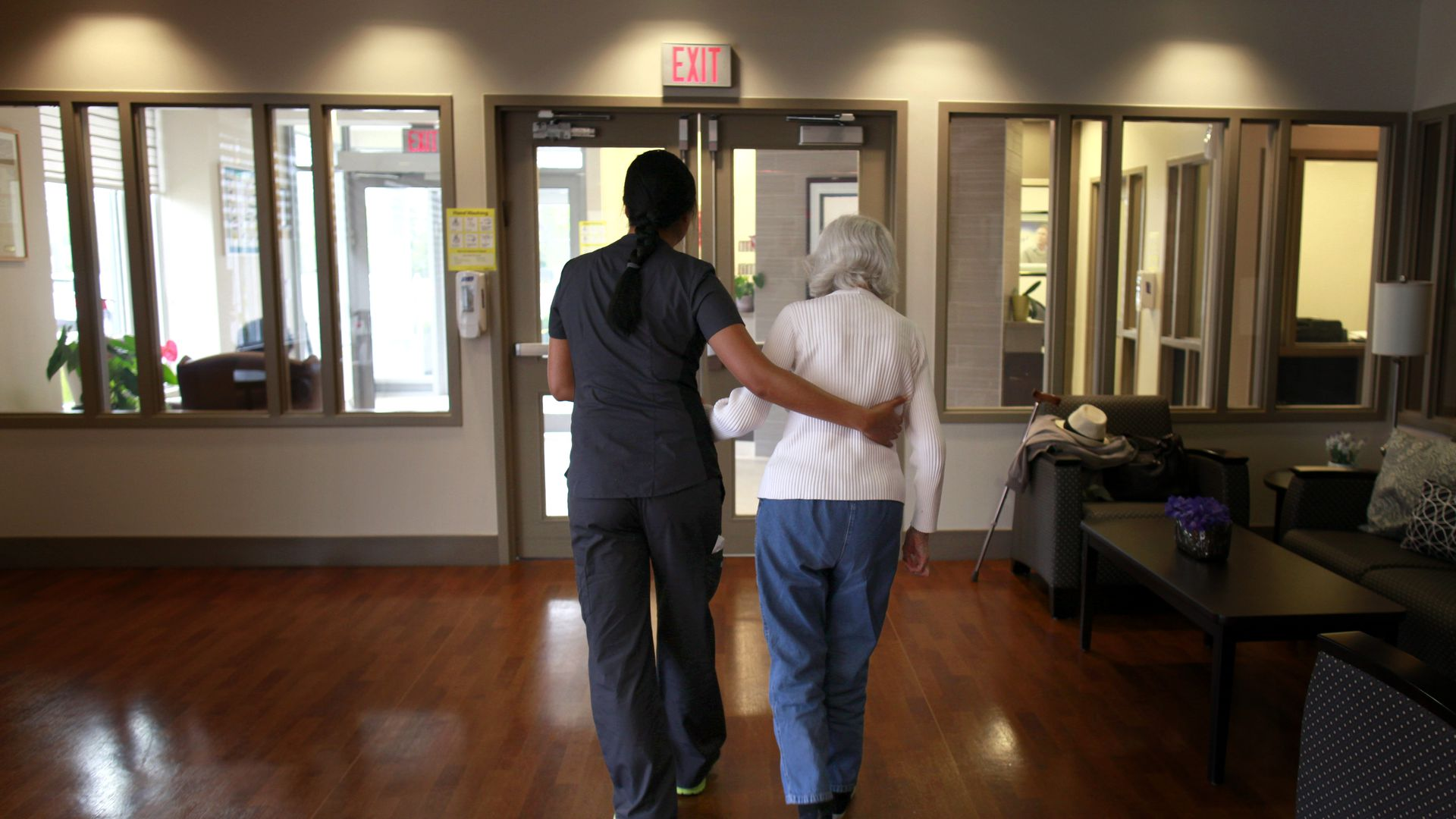 Photo of nurse walking an Alzheimer's patient down the hall, with her arm around her back