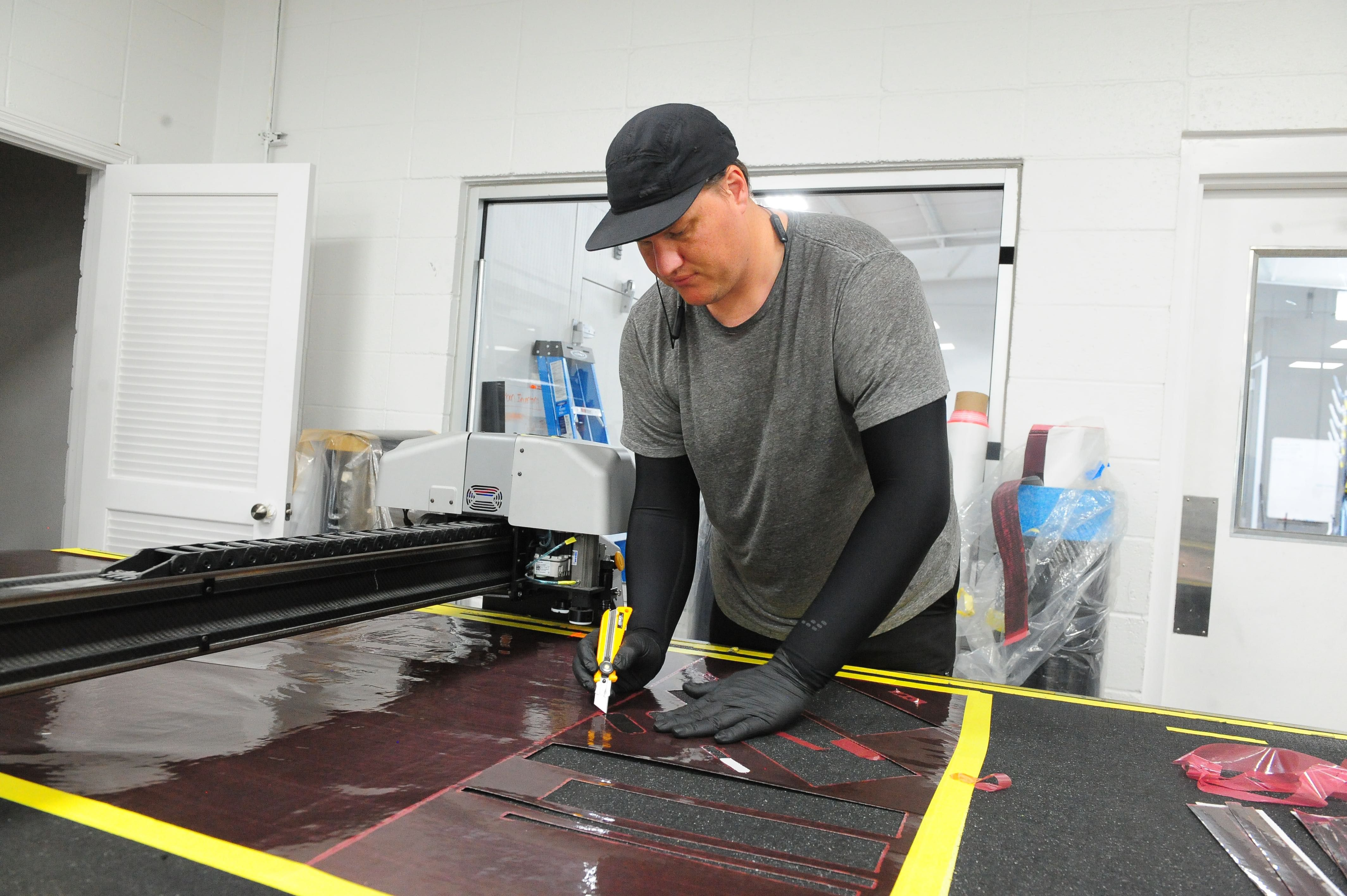 A worker cuts pieces of carbon from a sheet.