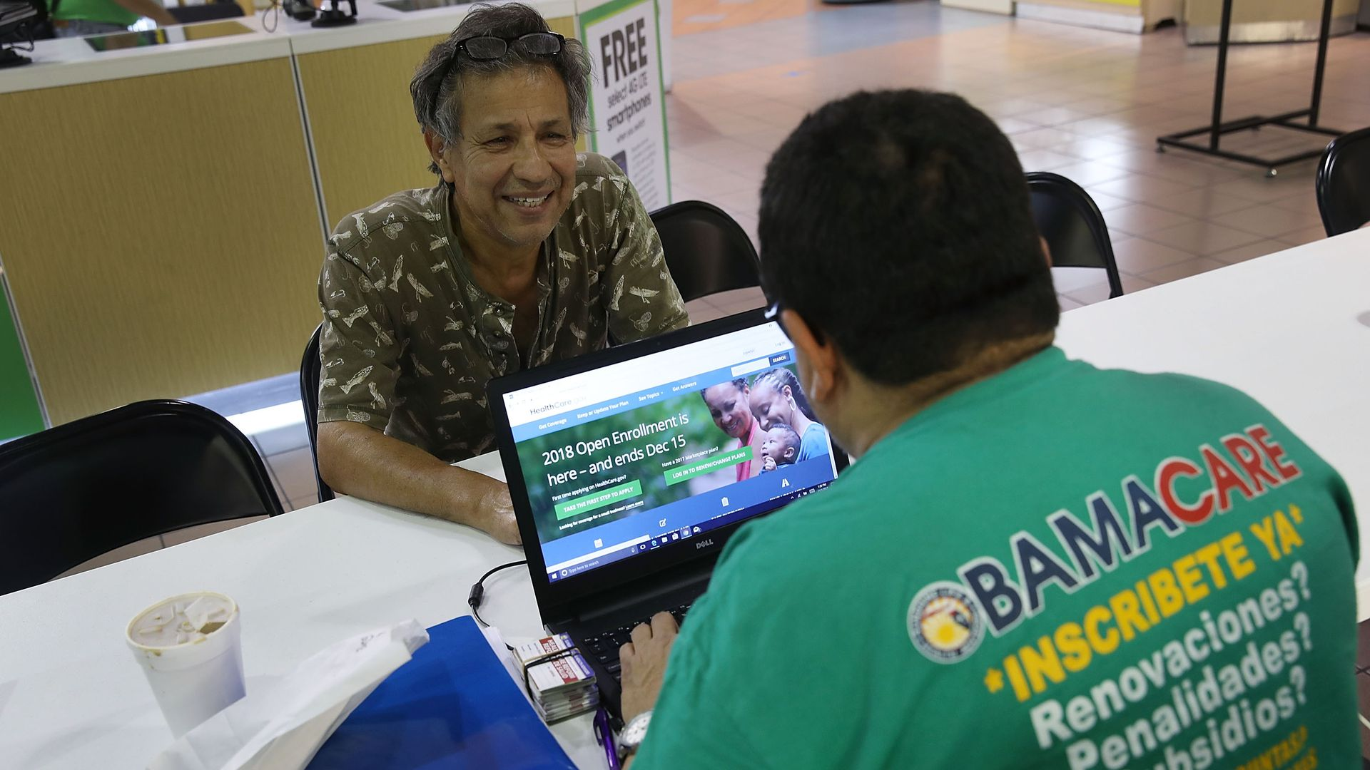An insurance agent helps a consumer sign up for an Obamacare plan.