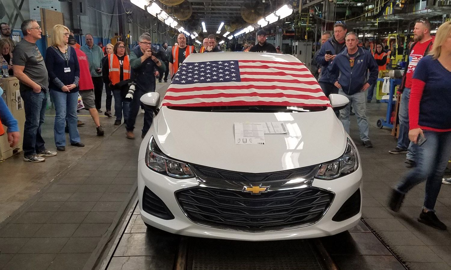 An American flag fills up the windshield of a white Chevy Cruze.