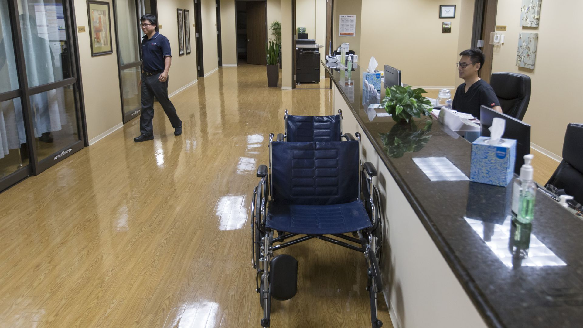 A nurse sits behind a desk in an emergency room with wheelchairs nearby.