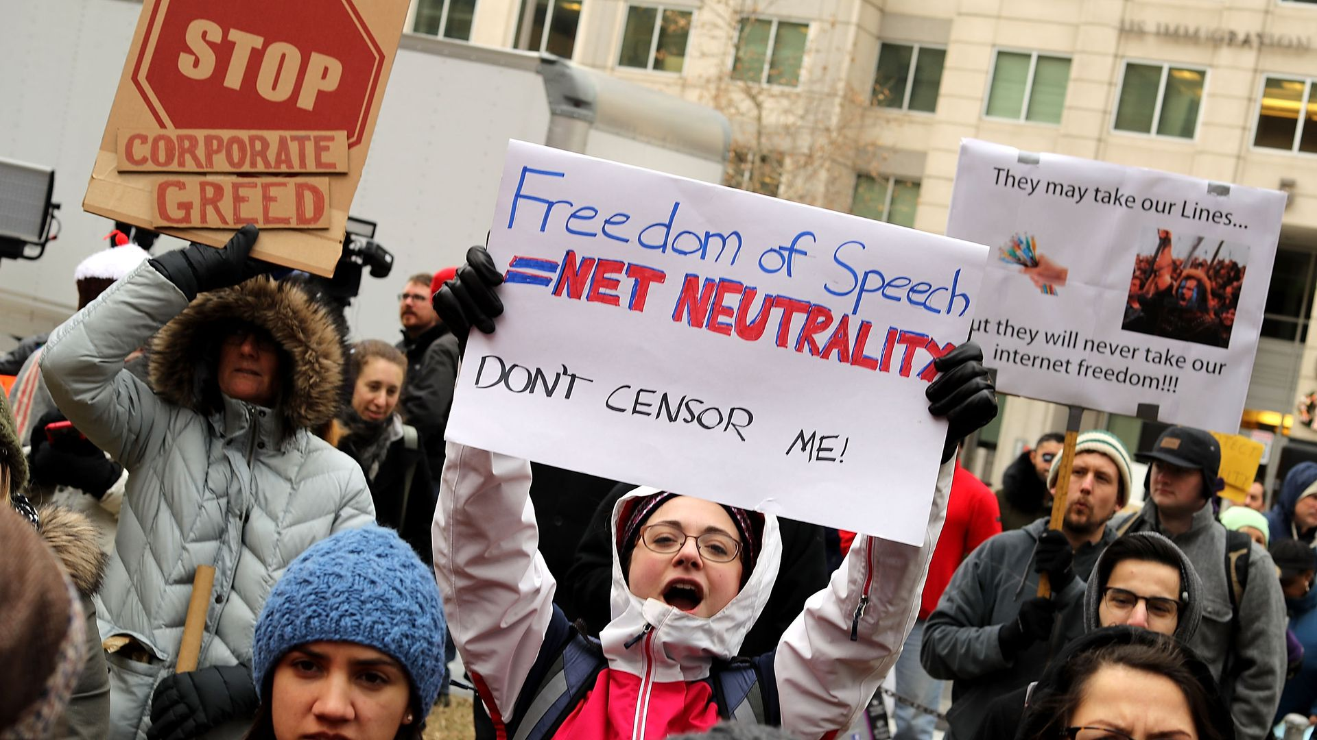 Protestors hold signs demonstrating against the end of net neutrality rules