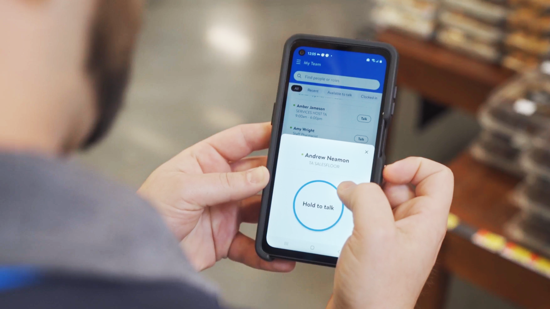A man holds a smartphone that shows Walmart's new app for employees