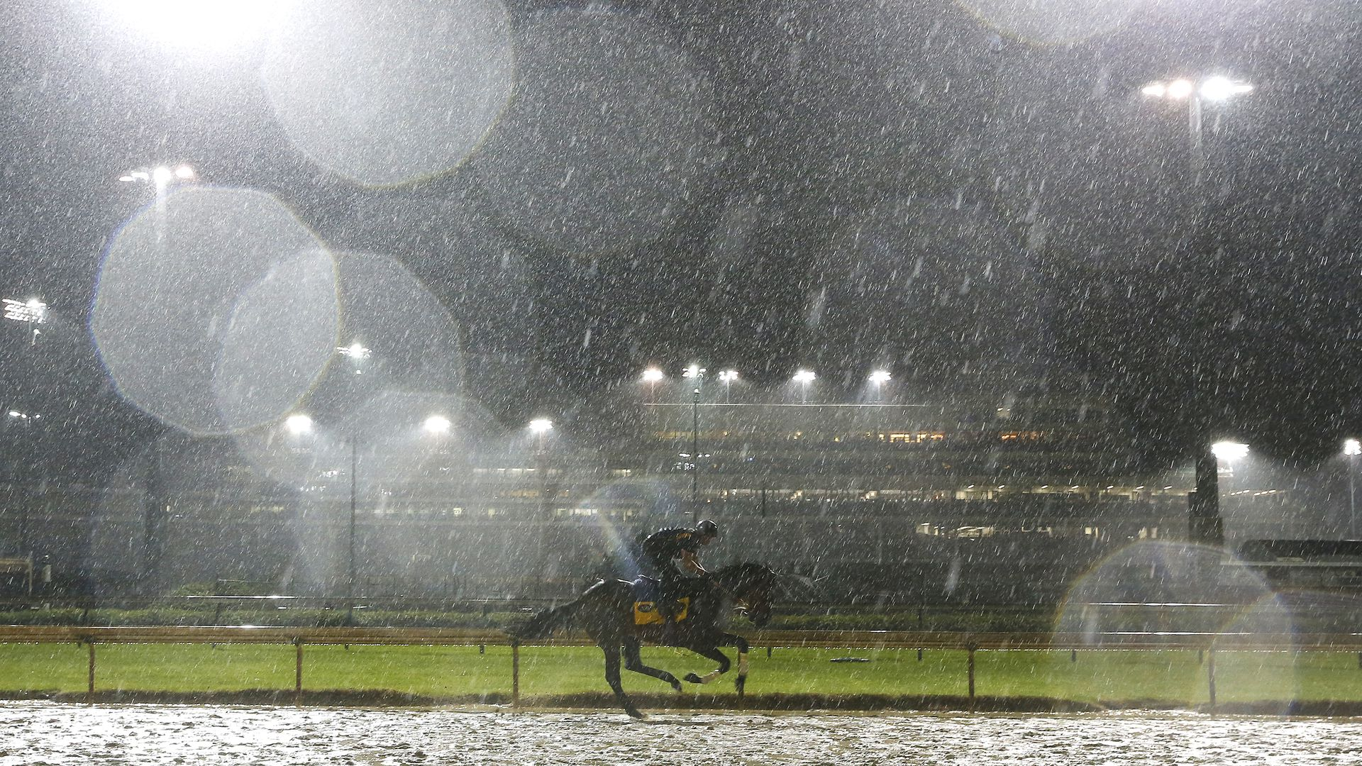 In this image, a racer rides a horse on an empty race track in the rain at night.
