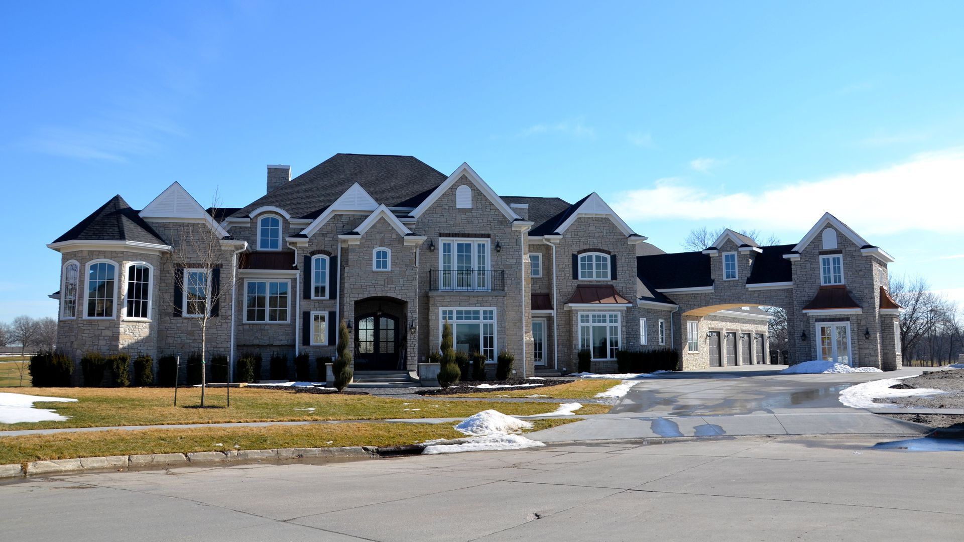 Sprawling grey brick mansion.