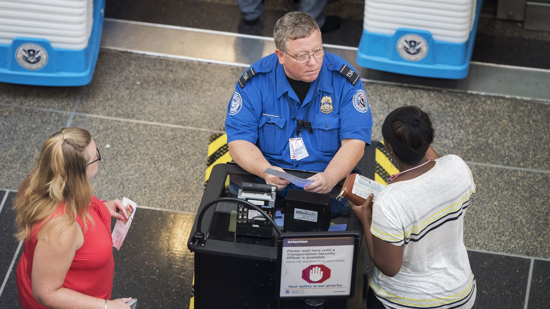 In this image, a TSA officer sits and speaks to a passenger in a white shirt.