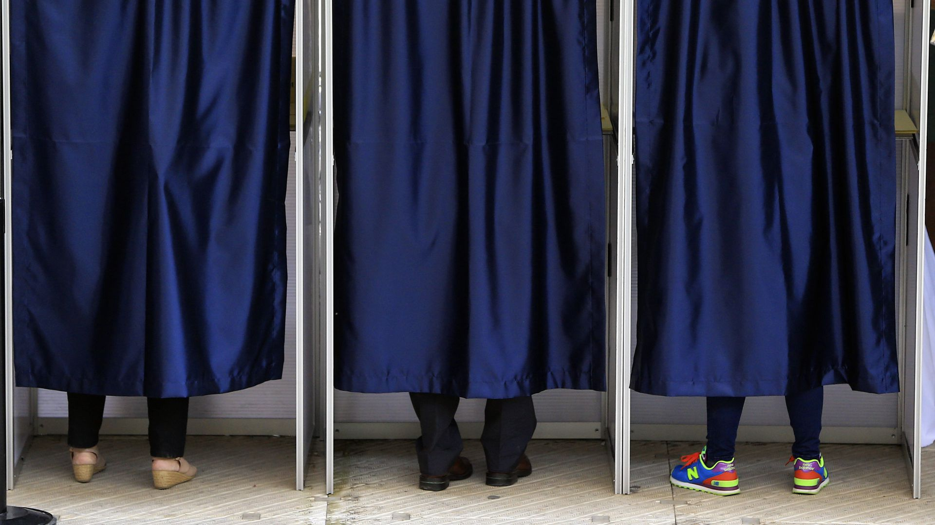 Blue curtains covering three voting booths. You can see the shoes of three different people at the bottom of each curtain