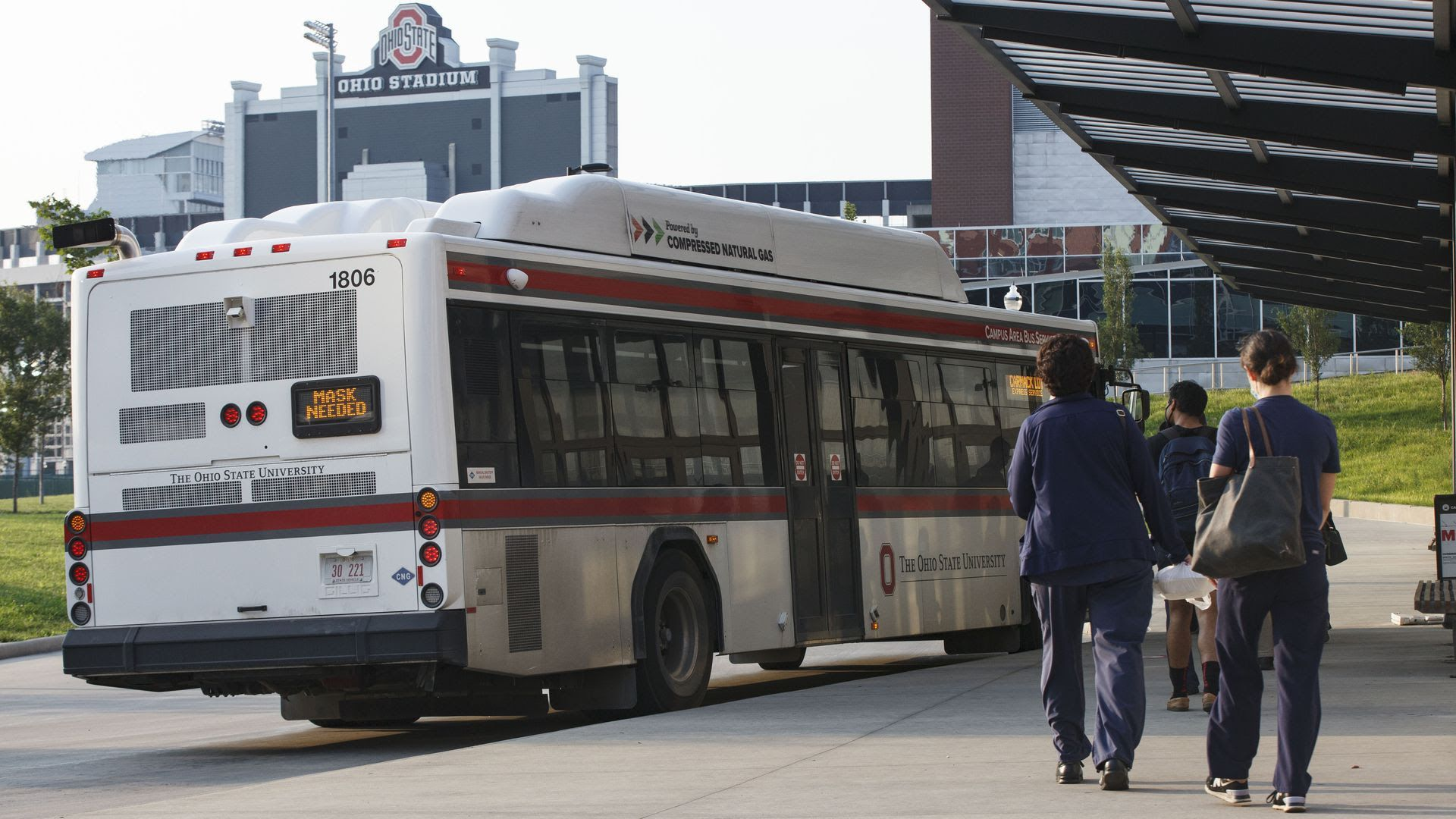 Students and medical workers line up to take a bus on the Ohio State University campus.