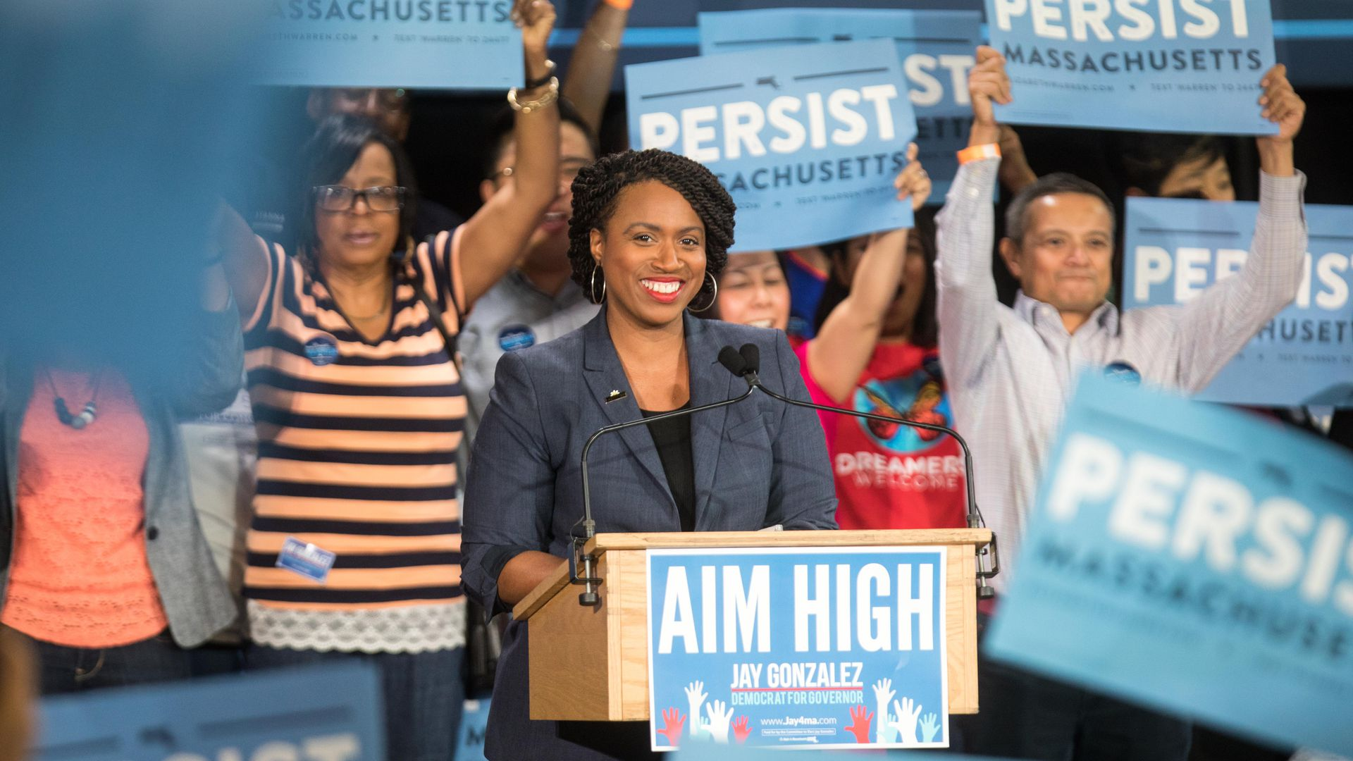 "Ayanna Pressley at a campaign rally, surrounded by ""Persist"" signs."
