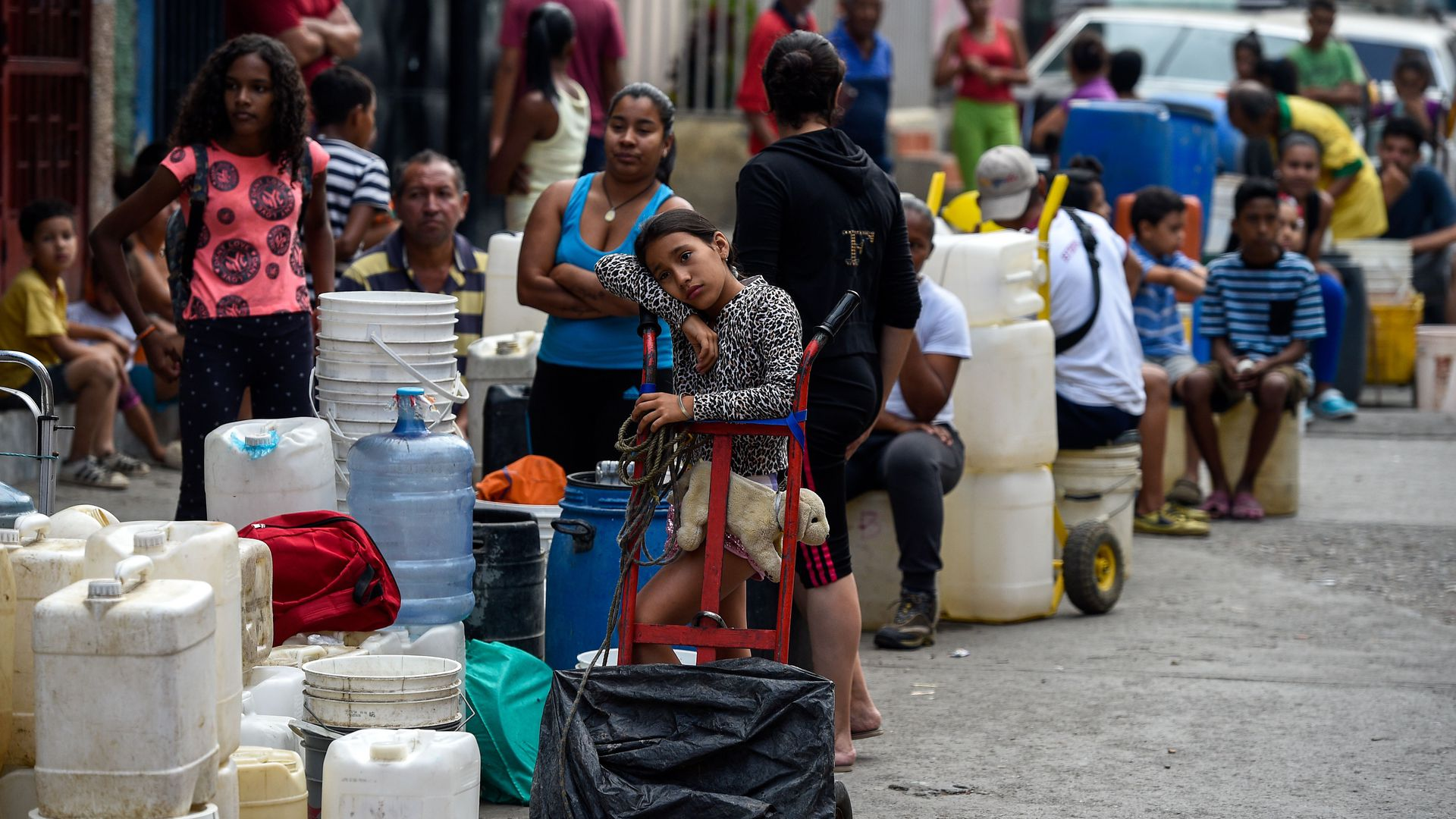 People line up with cans and tanks to collect water, at Petare neighborhood in Caracas