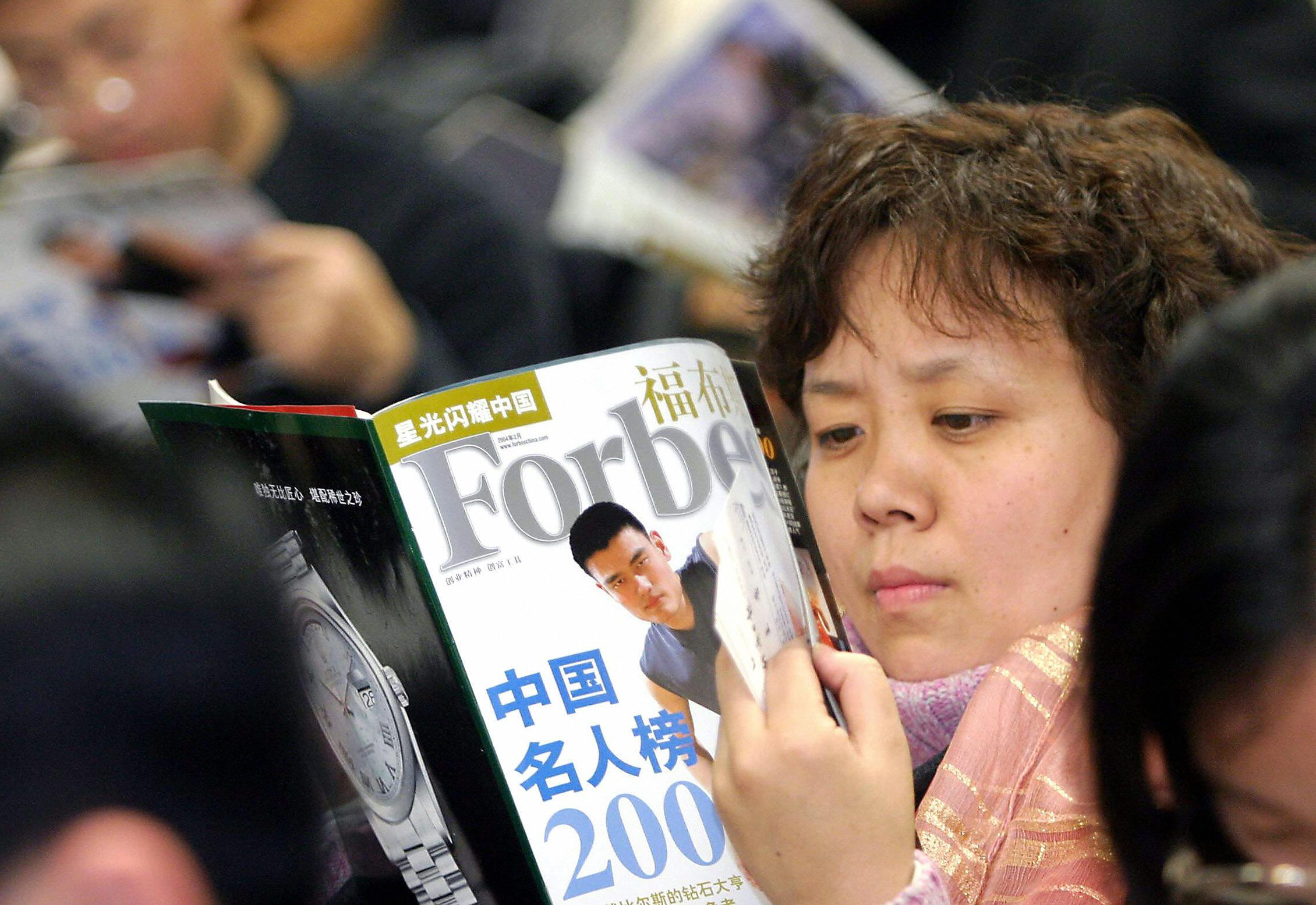 A Chinese woman reads Forbes