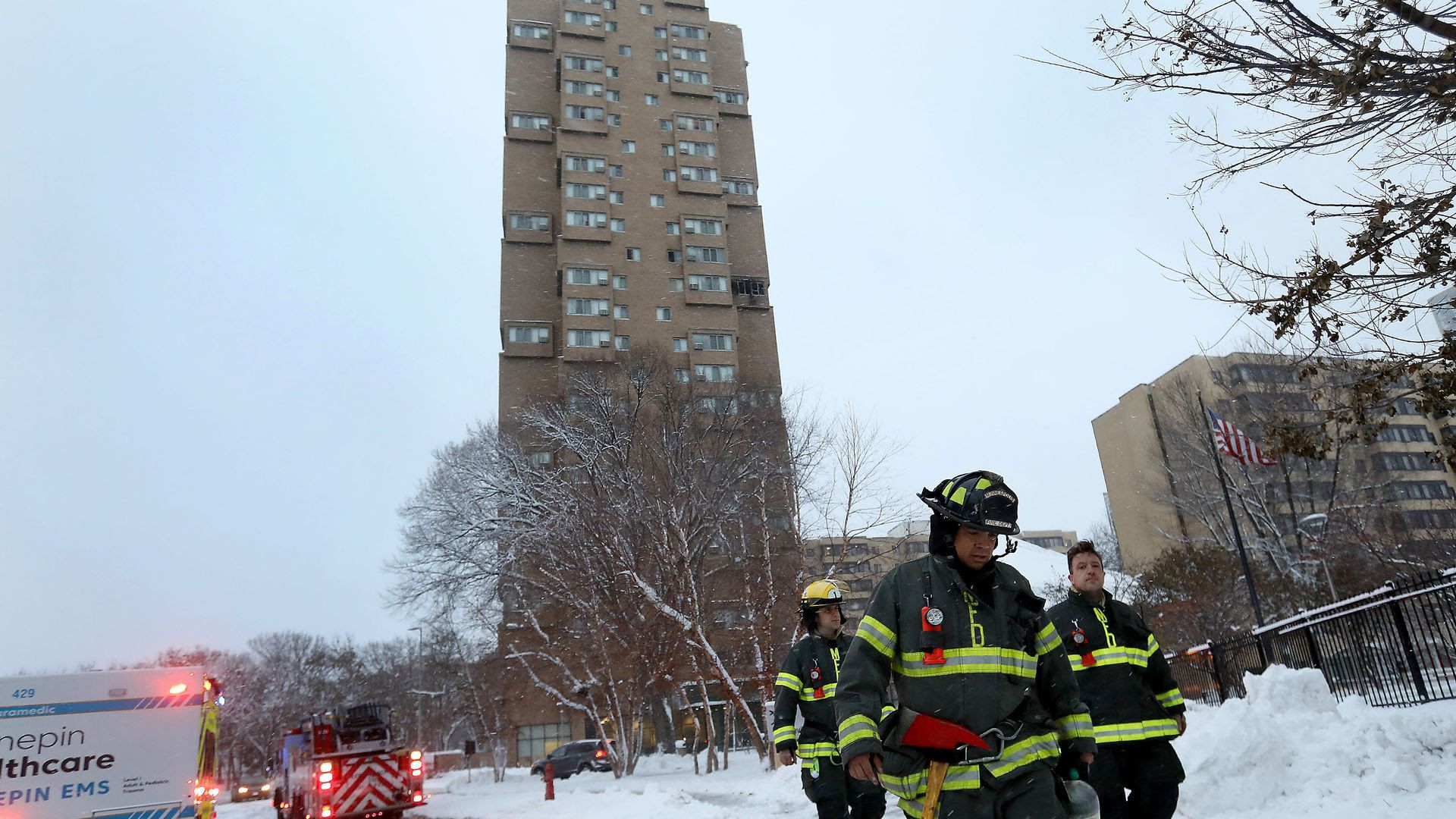 Three Minneapolis firefighters leave a high-rise building fire with their heads down on a snowy winter day.