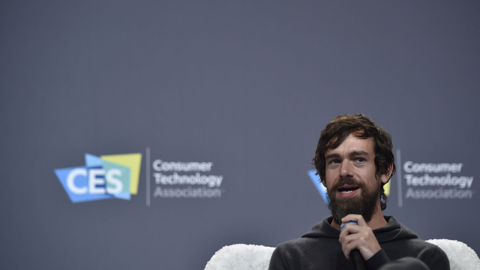 In this image, Twitter CEO Jack Dorsey sits in front of a dark gray wall at a conference, speaking into a microphone.