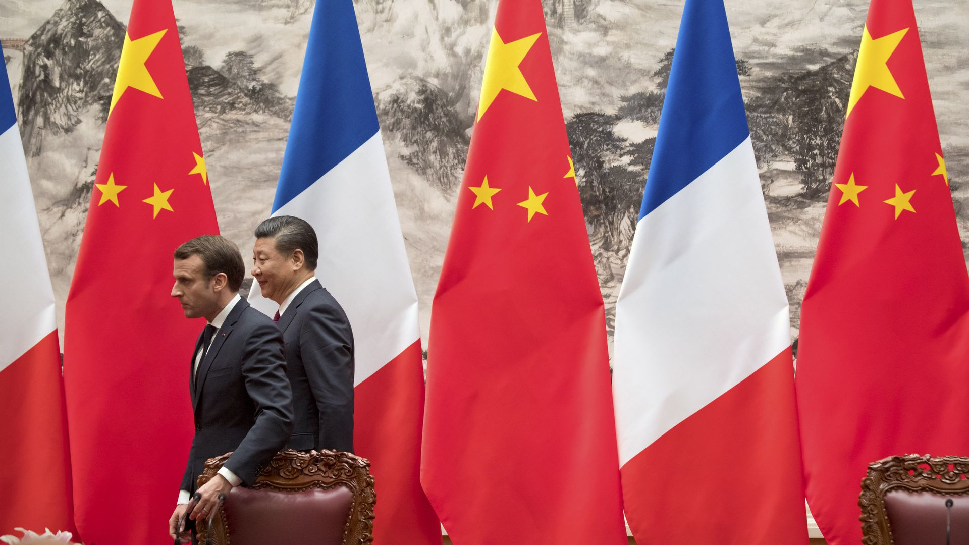 Macron and Xi walk out of a room decorated with French and Chinese flags