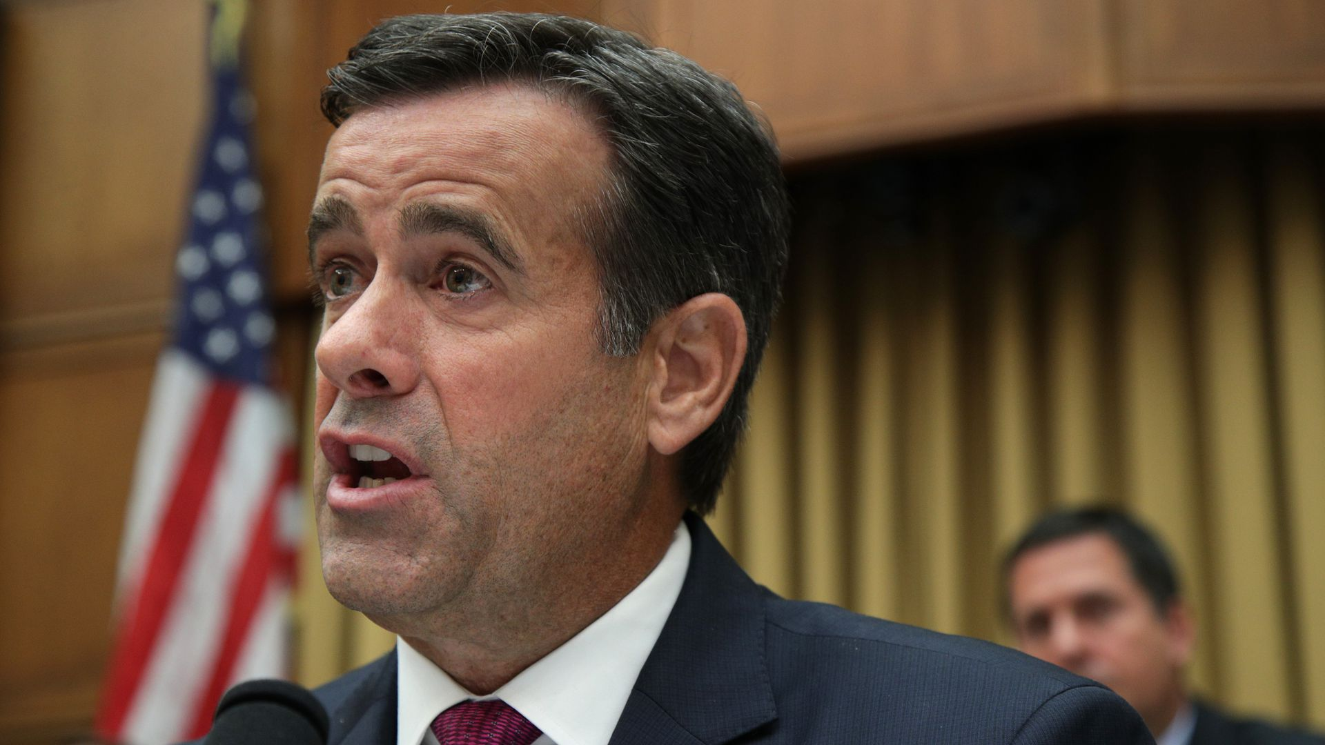 This image shows Ratcliffe speaking while wearing a suit at a hearing.