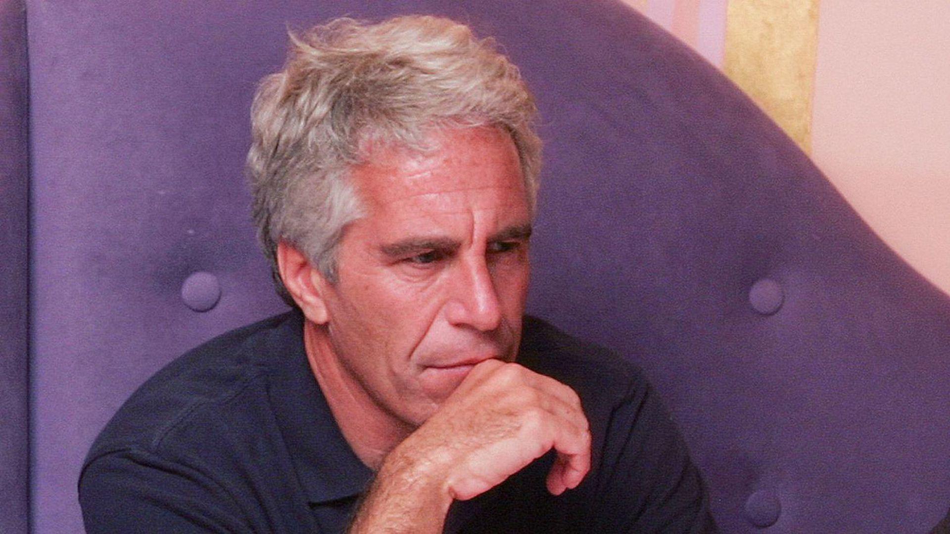 Jeffrey Epstein sits on a sofa.