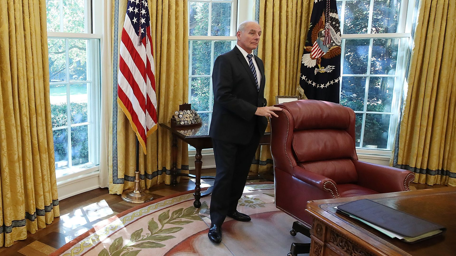 John Kelly stands behind the desk in the Oval Office