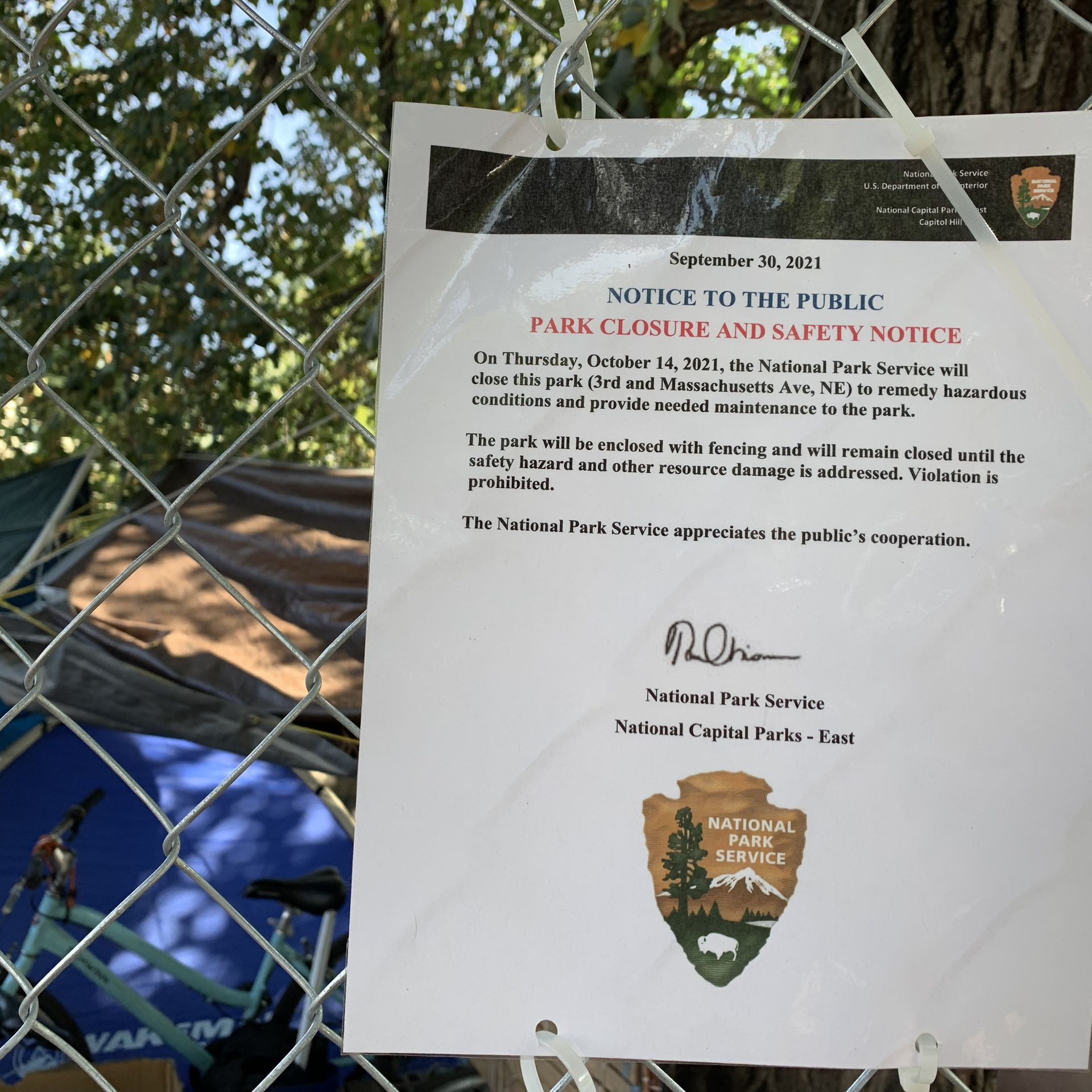 A sign attached to a fence detailing encampment clearing info.