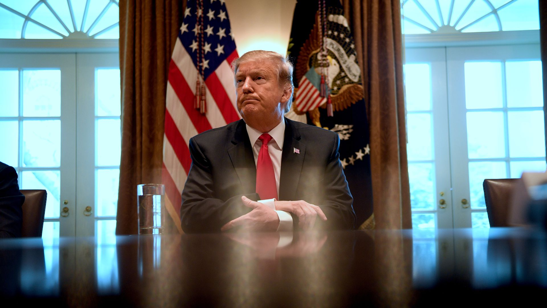 In this image, Trump sits at a desk with his hands folded and listens to someone out of view speak. There are two flags behind him.
