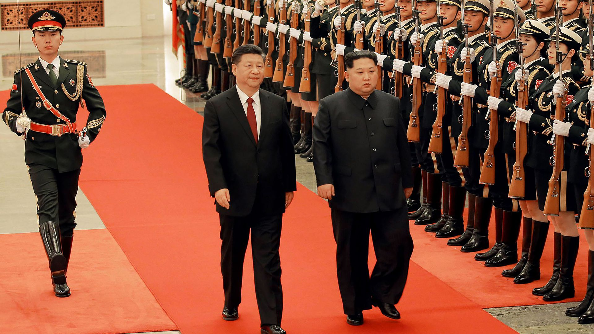 Chinese President Xi and North Korean Leader Kim march down red carpet next to line of soldiers together during their surprise meeting in Beijing