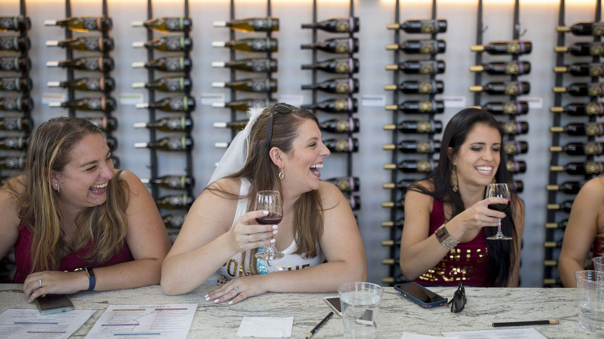 Women drink wine at a bar during a bachelorette party