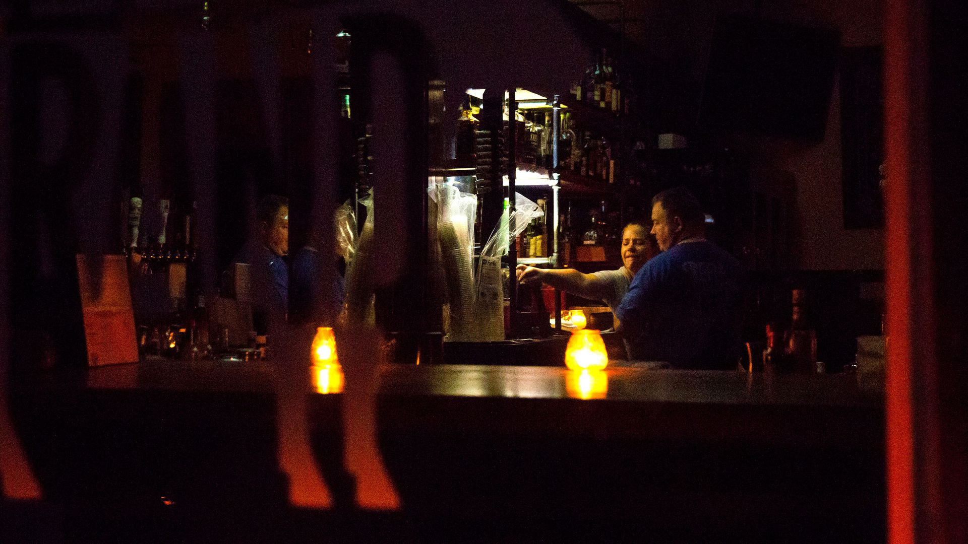 In this image, a bartender serves a customer at a darkened bar.