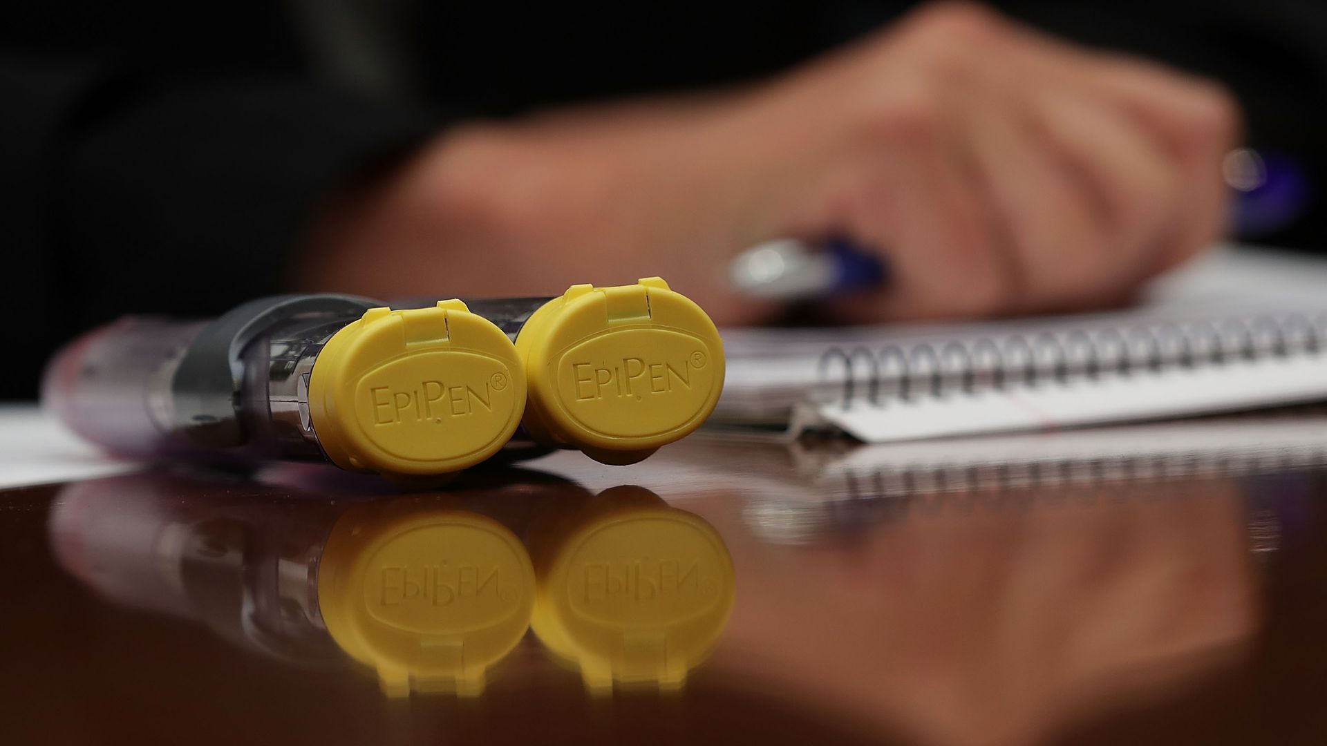 A pair of EpiPen's on a table.