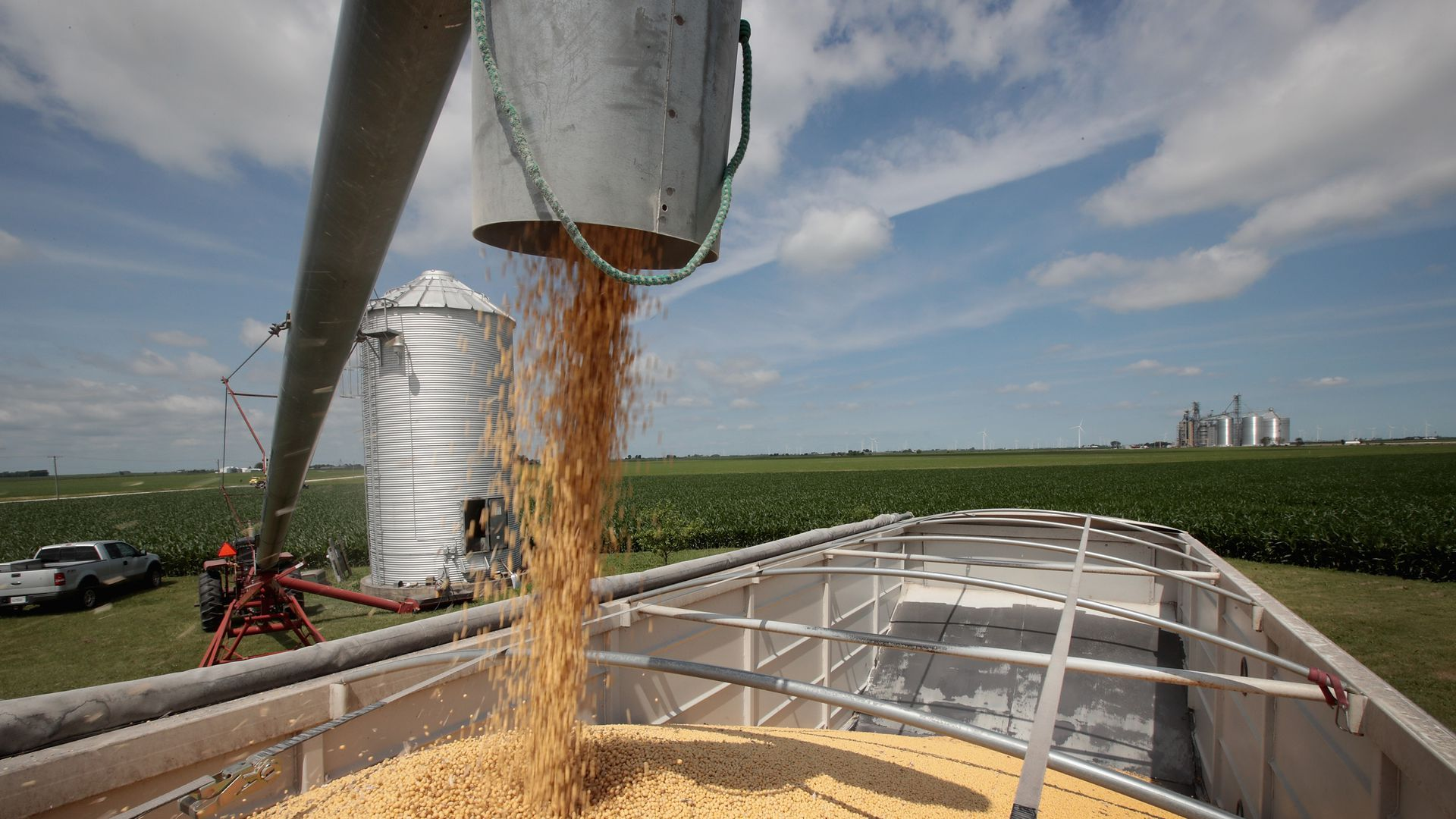 A bucket dumps soybeans into a truck