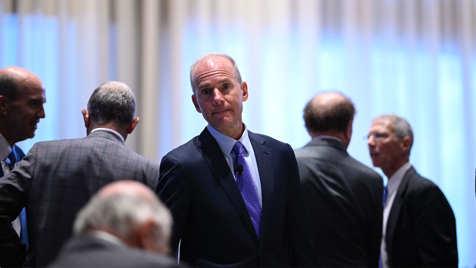 In this image, Muilenburg stands in the midst of a crowd that is facing the opposite direction. He is facing the camera.