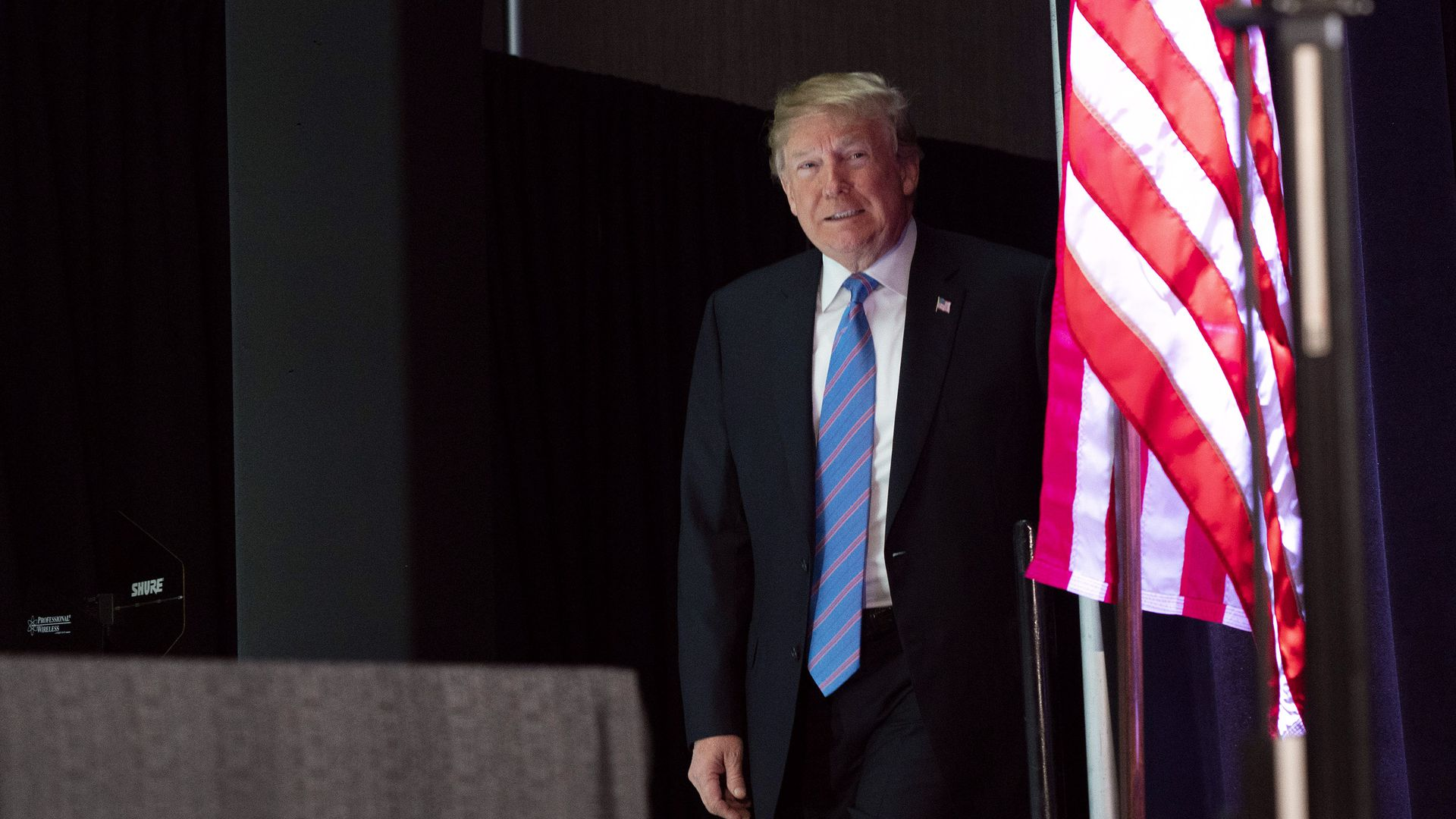 Donald Trump walking on stage peering from behind an American Flag
